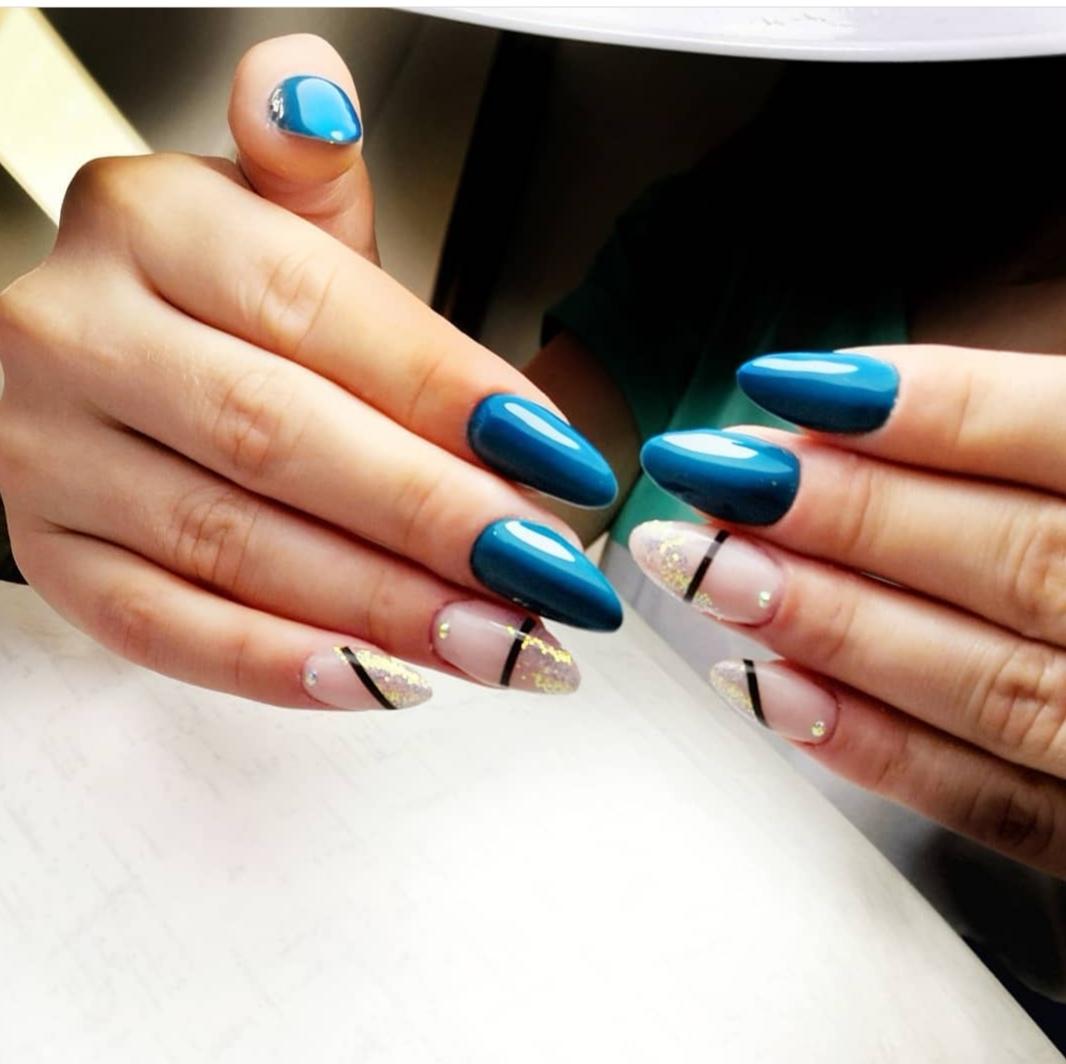 Маникюр с золотой фольгой и полосками в синем цвете на длинные ногти.