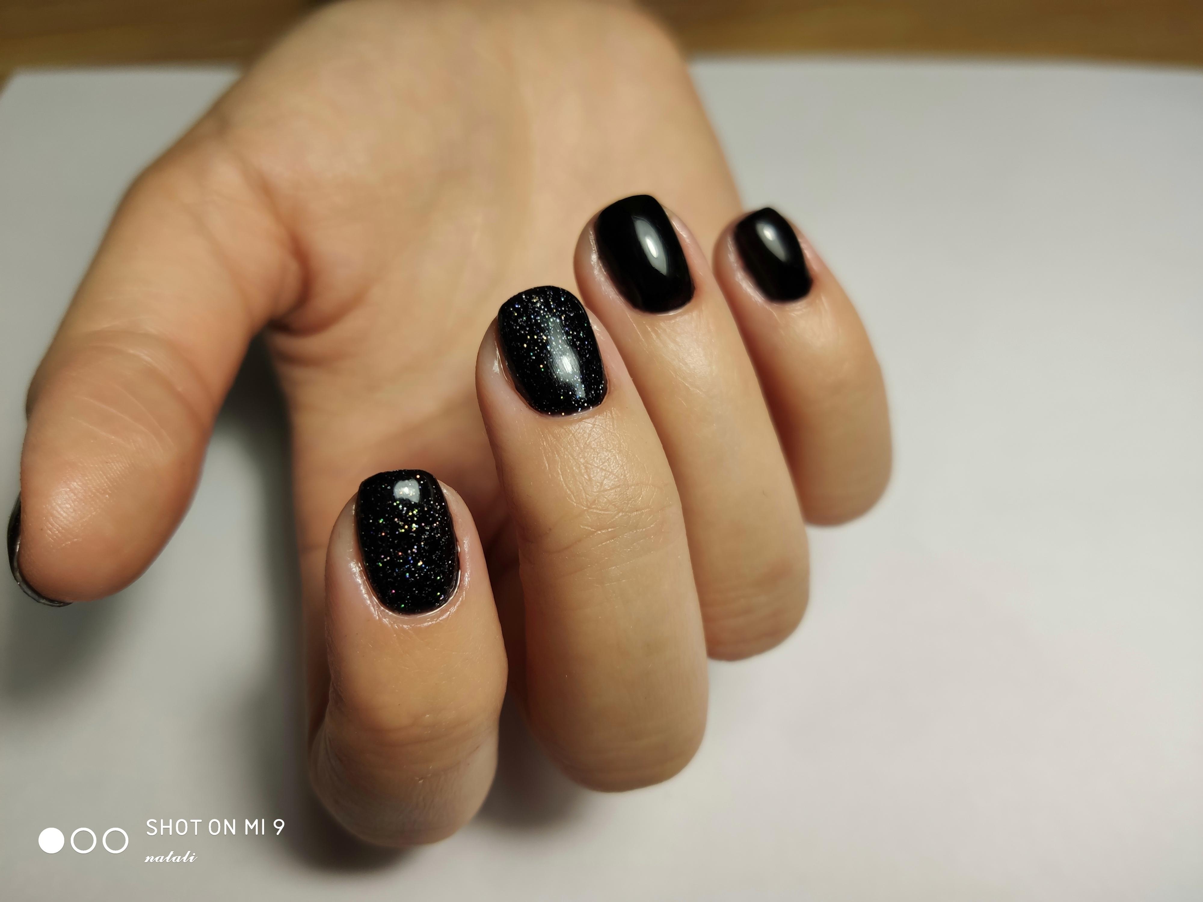 Маникюр с блестками в черном цвете.