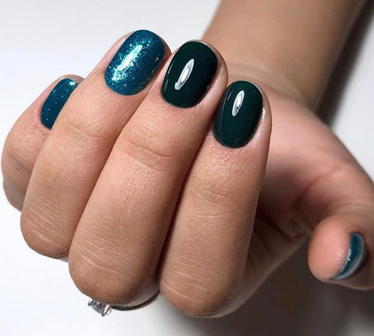 Маникюр в тёмно-зеленом цвете с блёстками.
