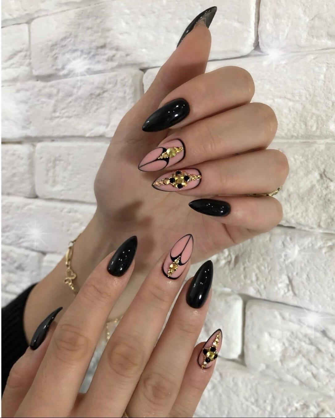 Маникюр с матовым дизайном и стразами в черном цвете на длинные ногти.