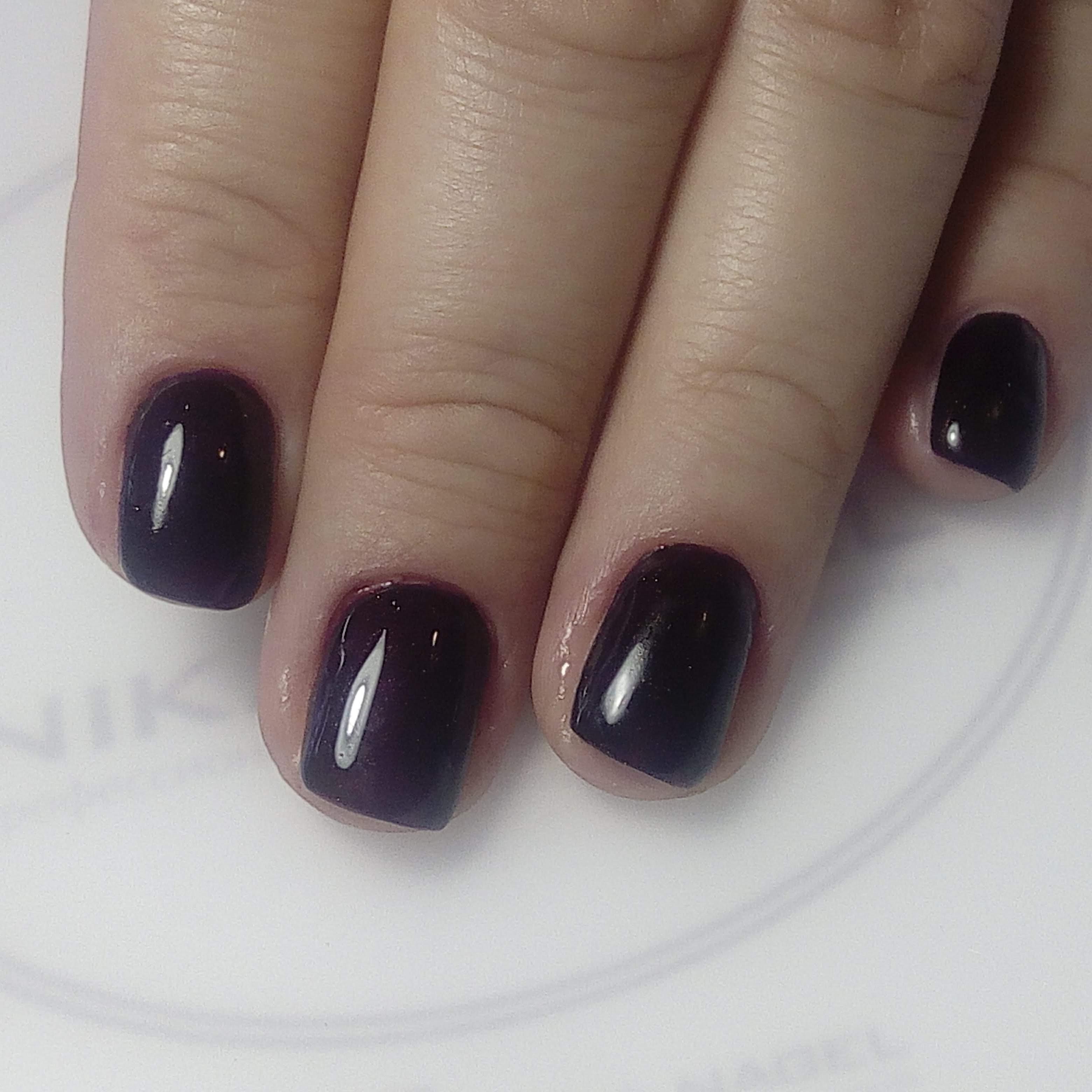Однотонный глянцевый маникюр в чёрном цвете на коротких ногтях.