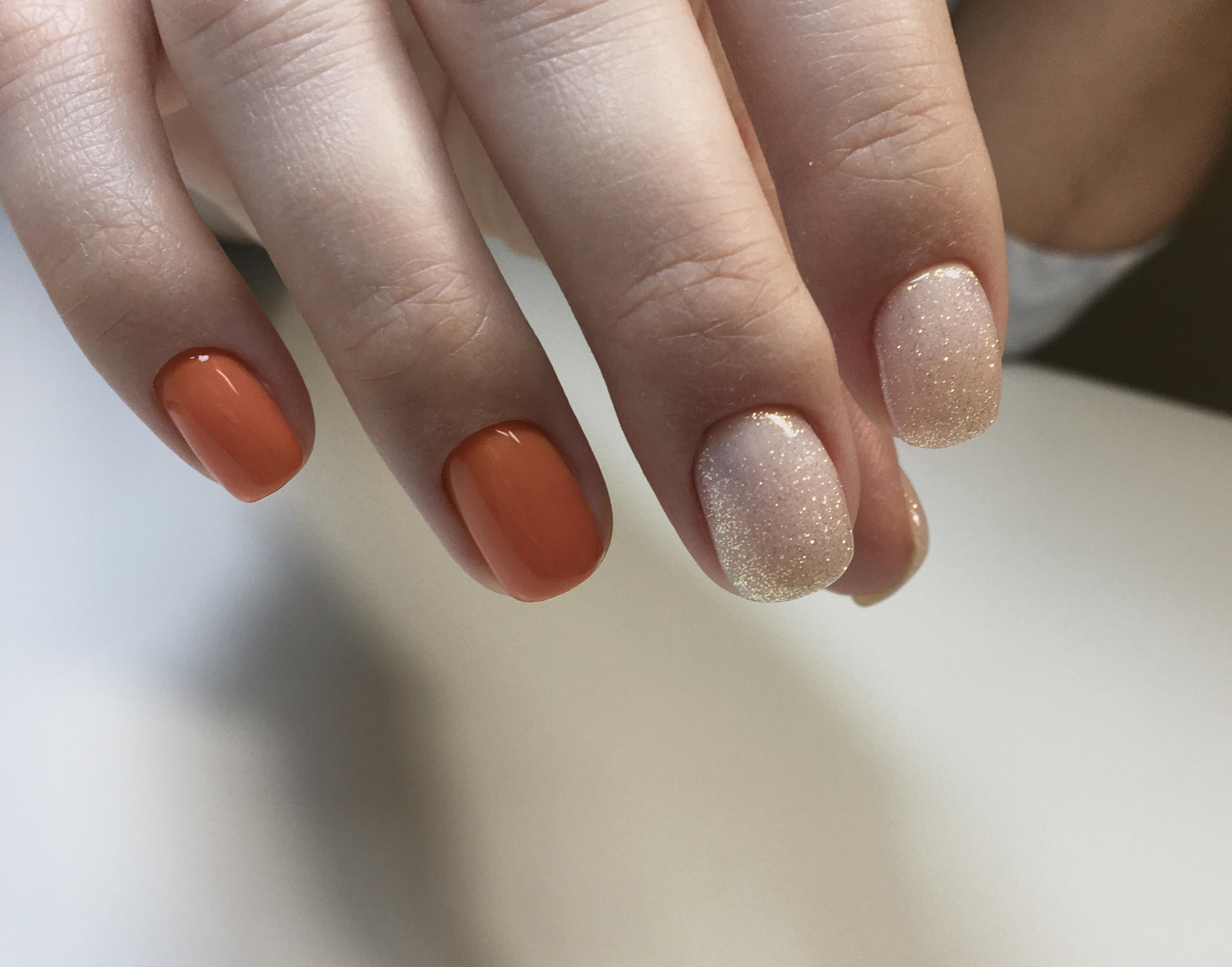 Нюдовый маникюр с блестками с оранжевым дизайном.