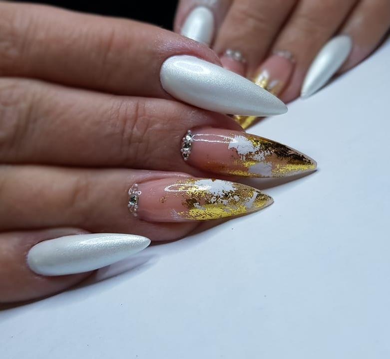 Маникюр с золотой фольгой и стразами в белом цвете.