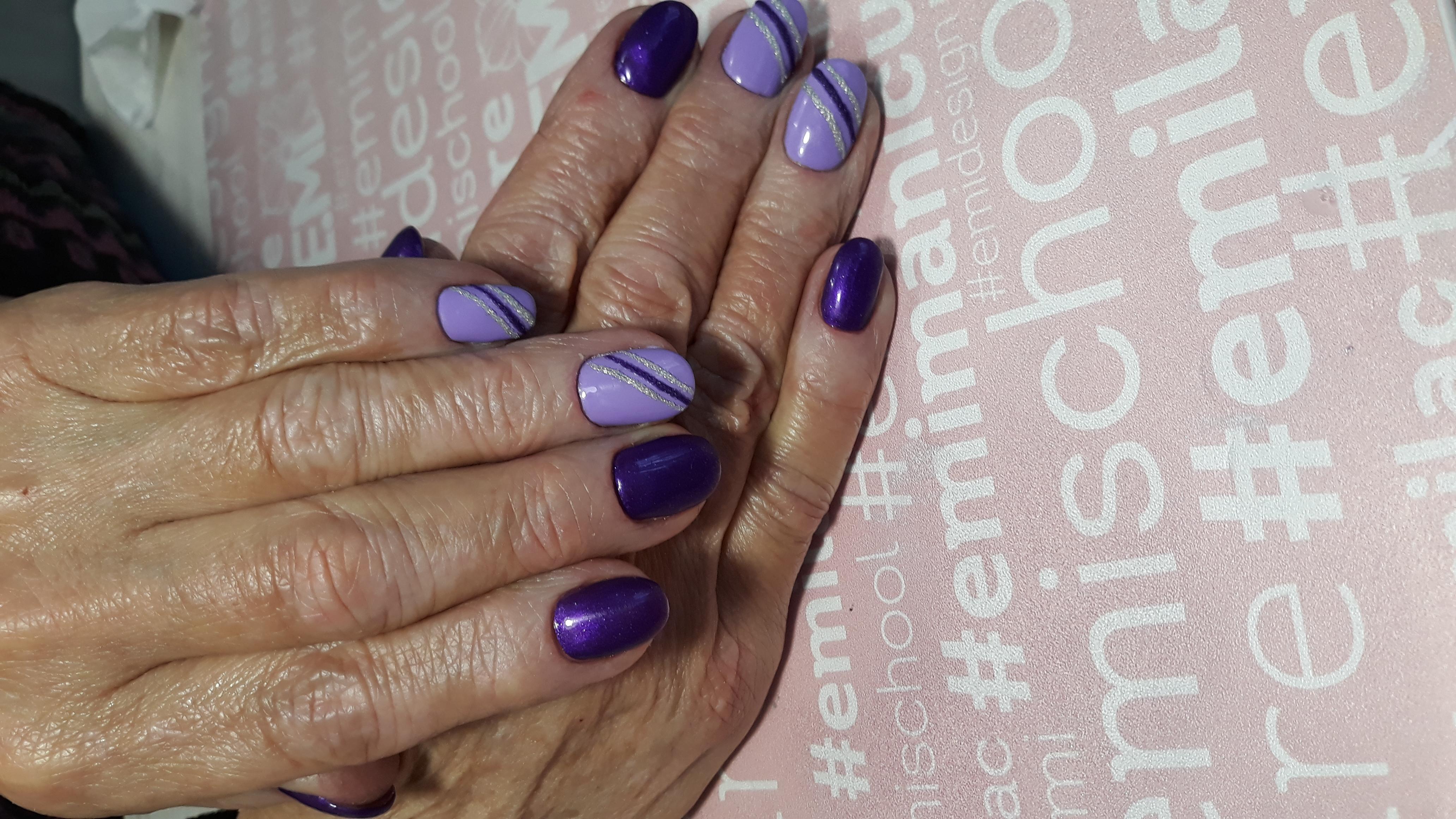 Маникюр в фиолетовом цвете с полосками и серебряными блёстками.