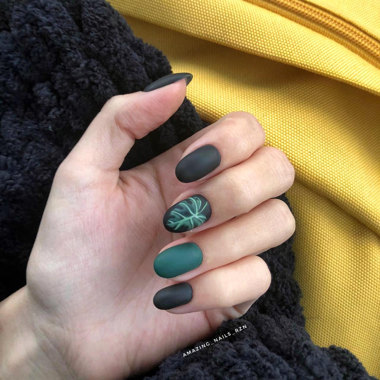 Матовый маникюр в чёрном цвете с тёмно-зелёным дизайном и растительным слайдером.