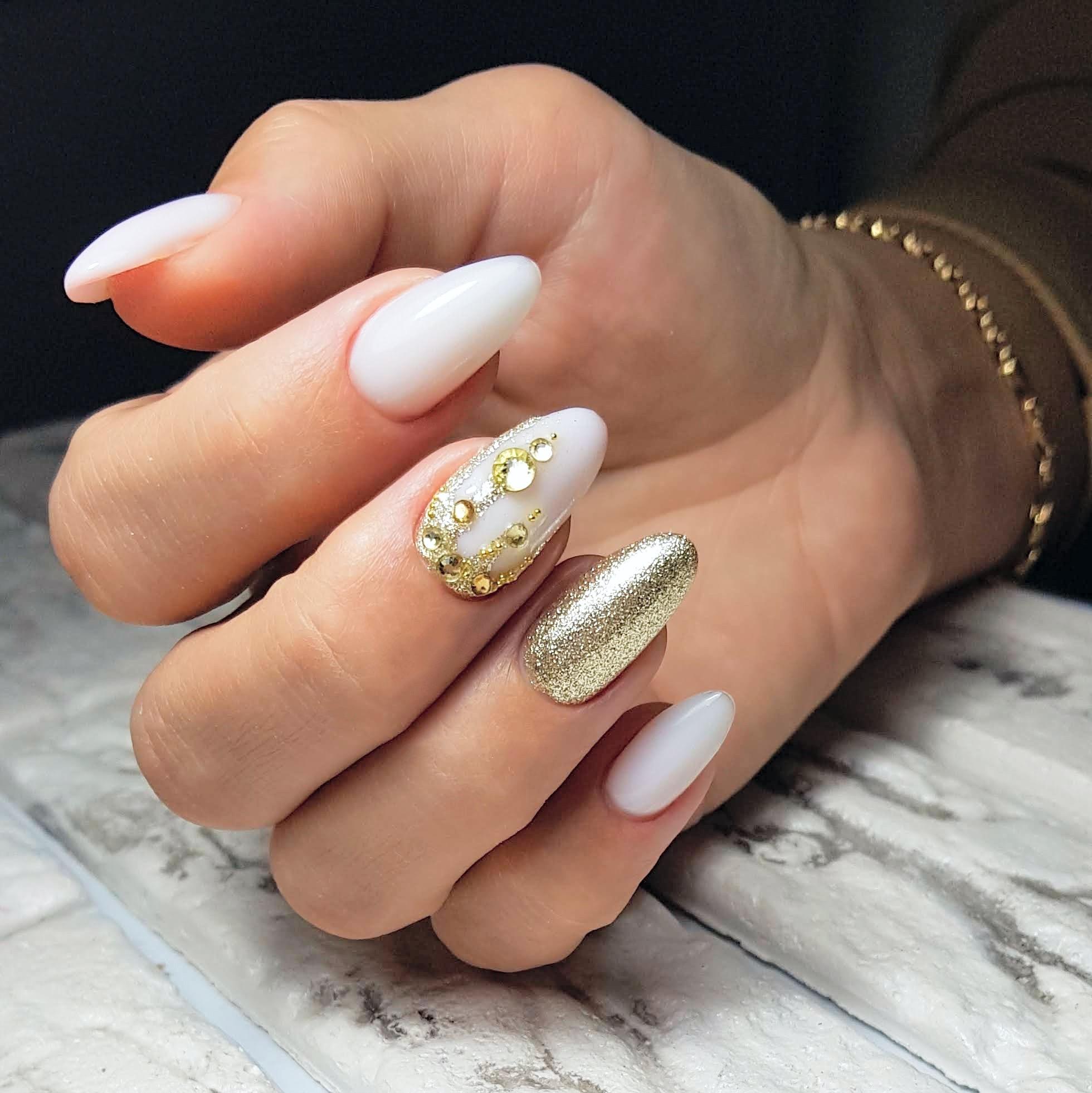 Маникюр с золотыми блестками и стразами в белом цвете.