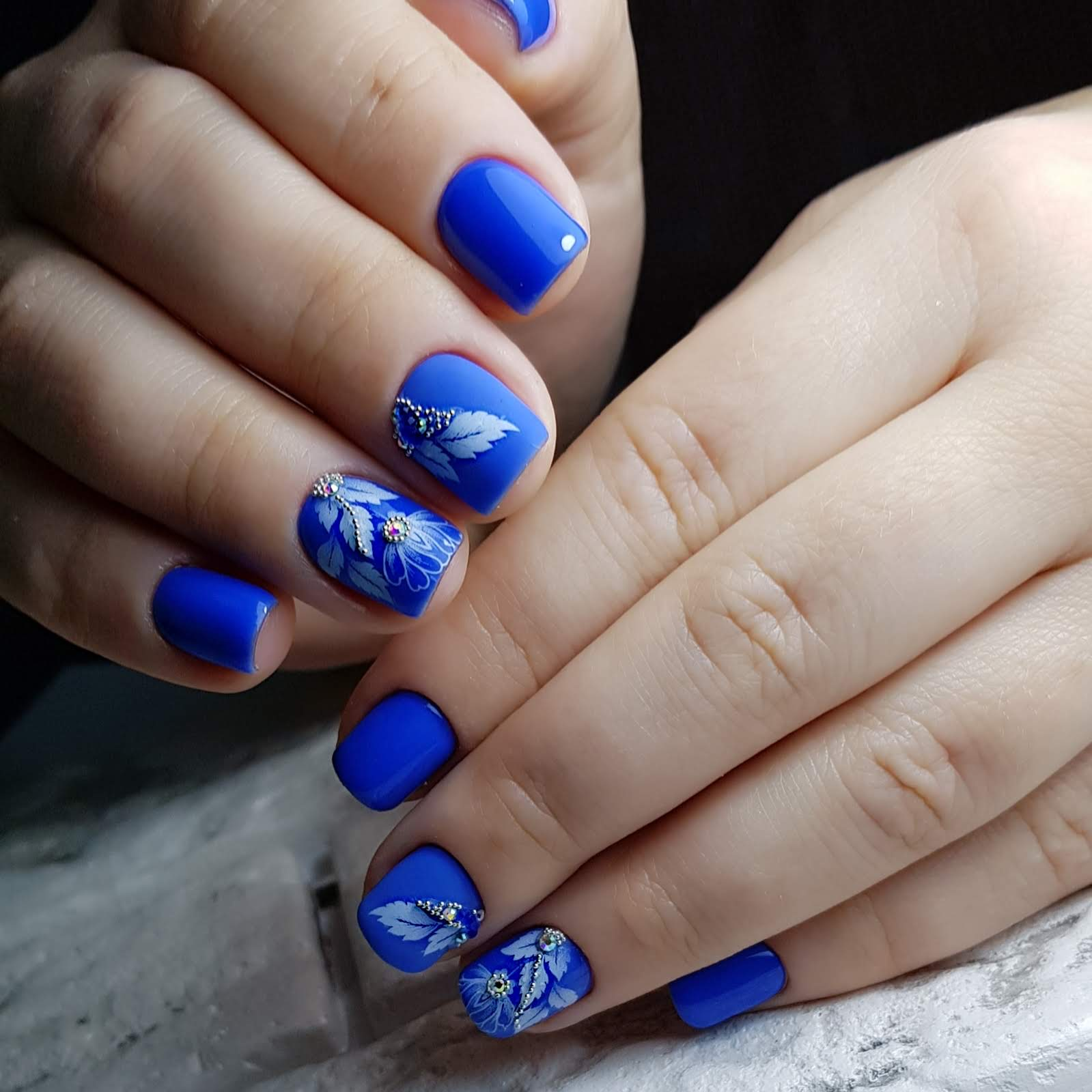 Маникюр с цветочным рисунком и стразами в синем цвете.