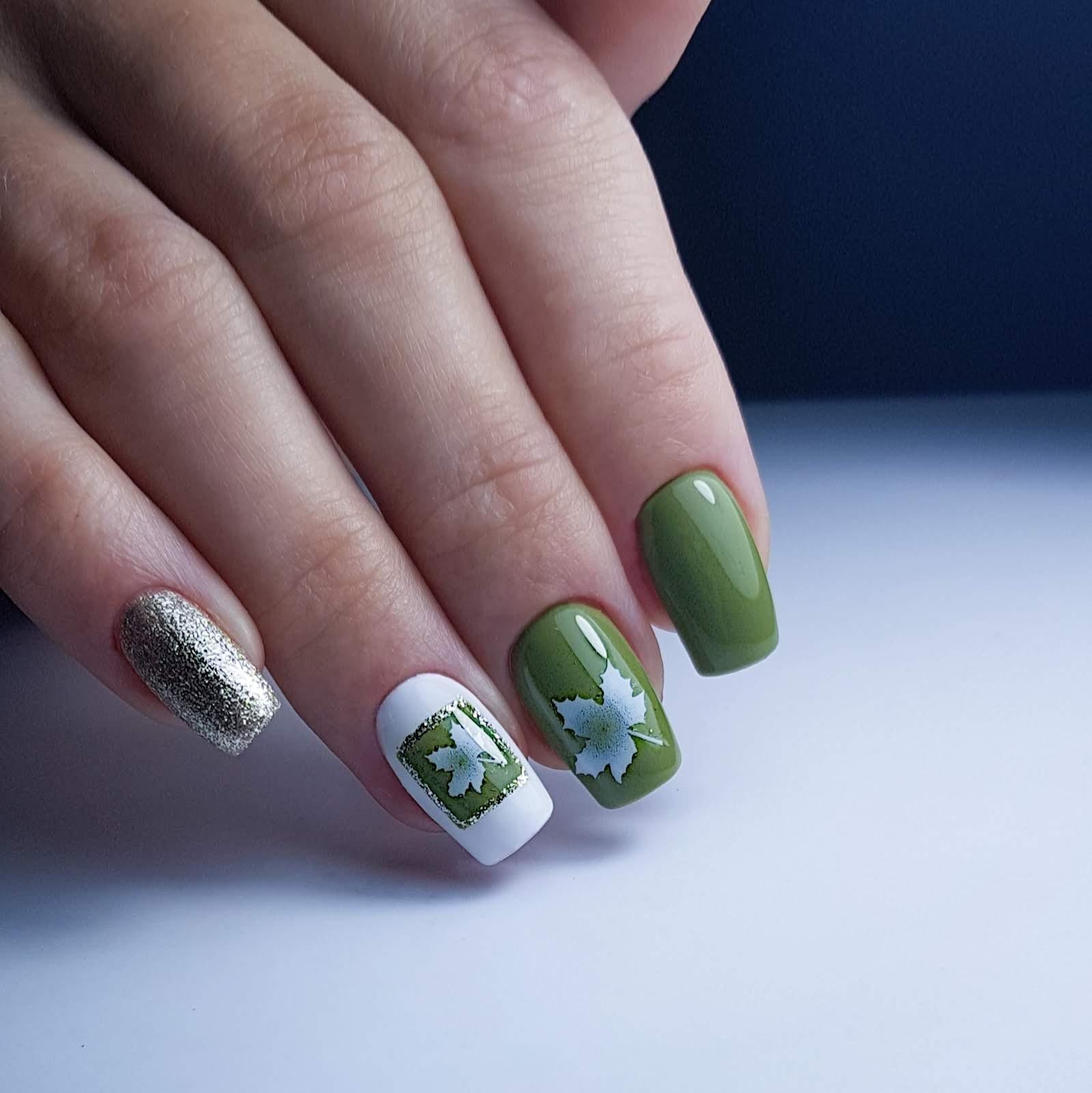 Маникюр с кленовым листом и золотыми блестками в зеленом цвете.