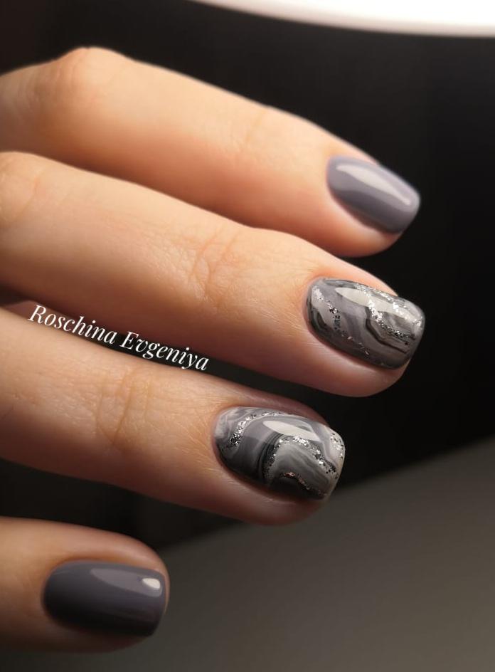 Маникюр с мраморным дизайном блестками в сером цвете на короткие ногти.
