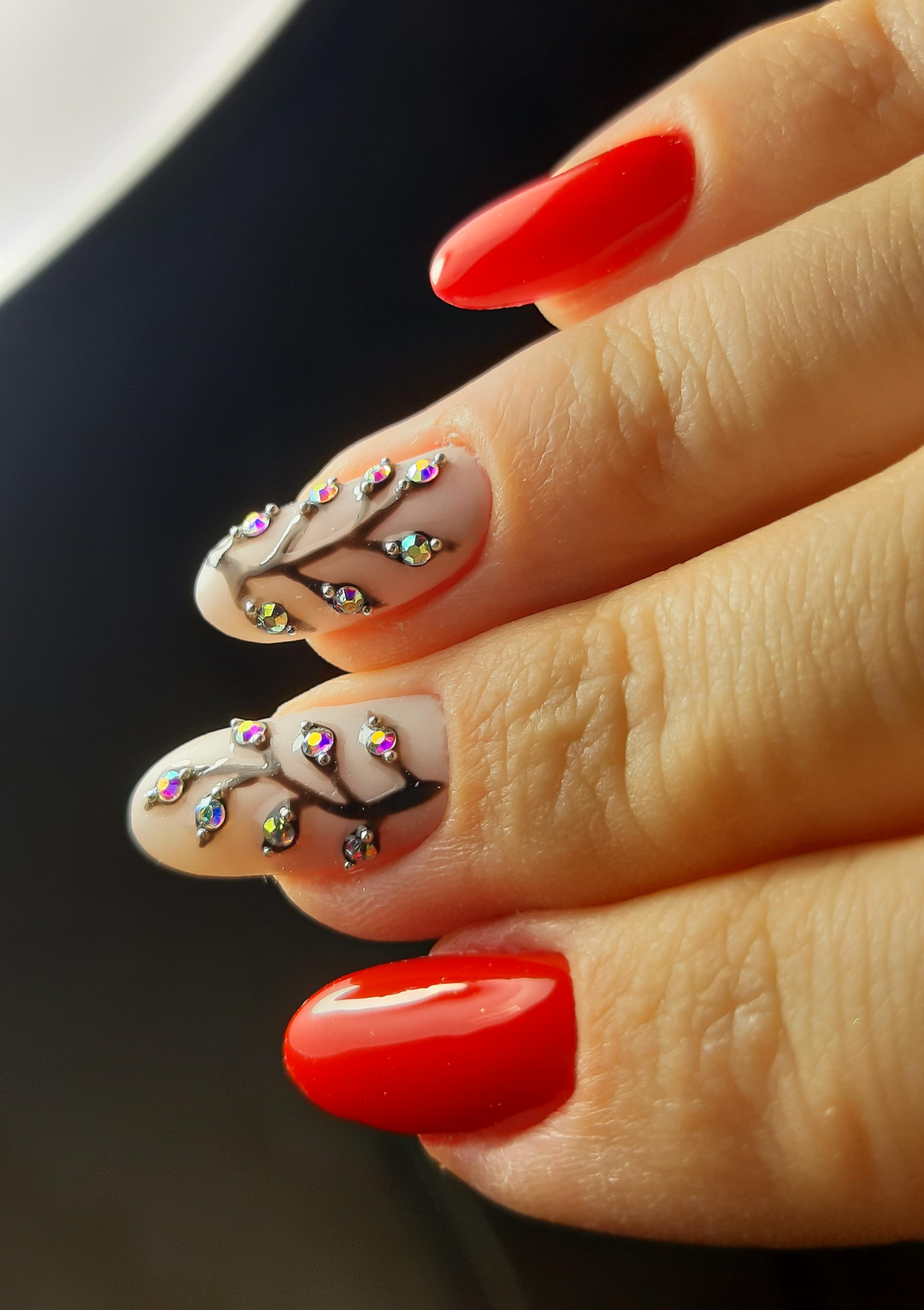 Маникюр с растительным рисунком и стразами в красном цвете на длинные ногти.