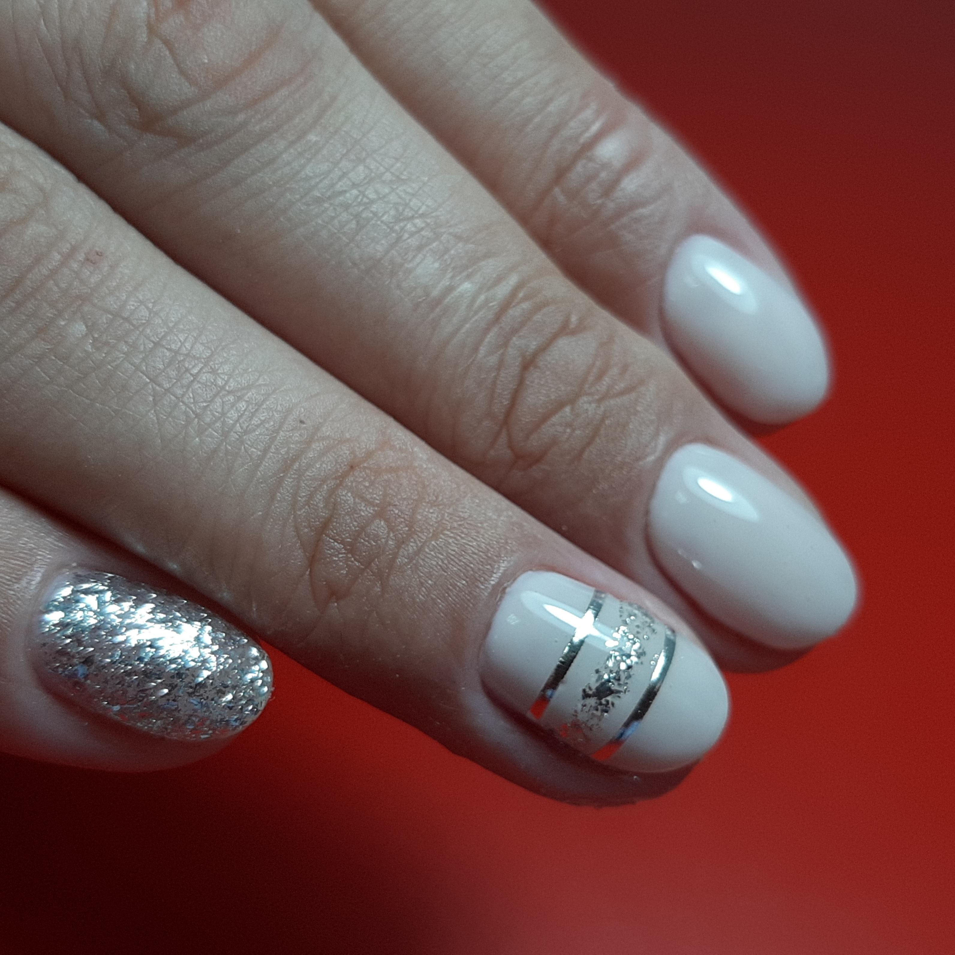 Маникюр с серебряными полосками и блестками в бежевом цвете на короткие ногти.