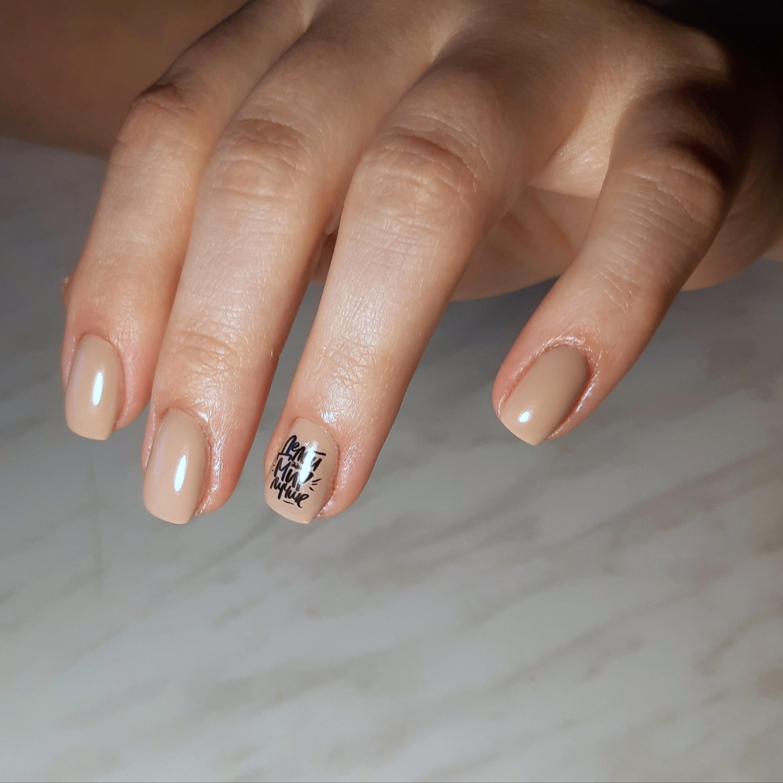 Маникюр с надписями в бежевом цвете на короткие ногти.