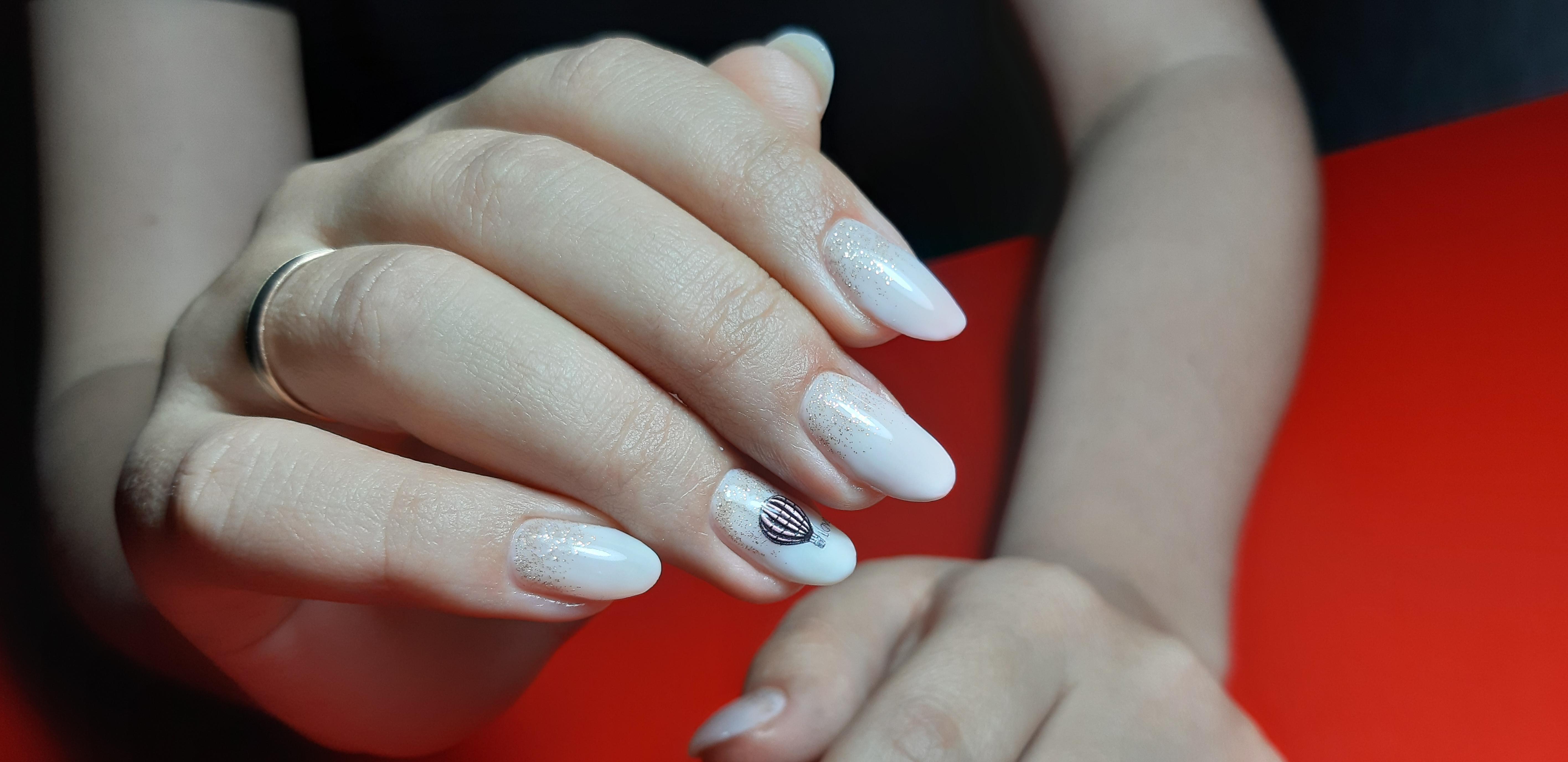 Маникюр со слайдерами и блестками в молочном цвете на длинные ногти.
