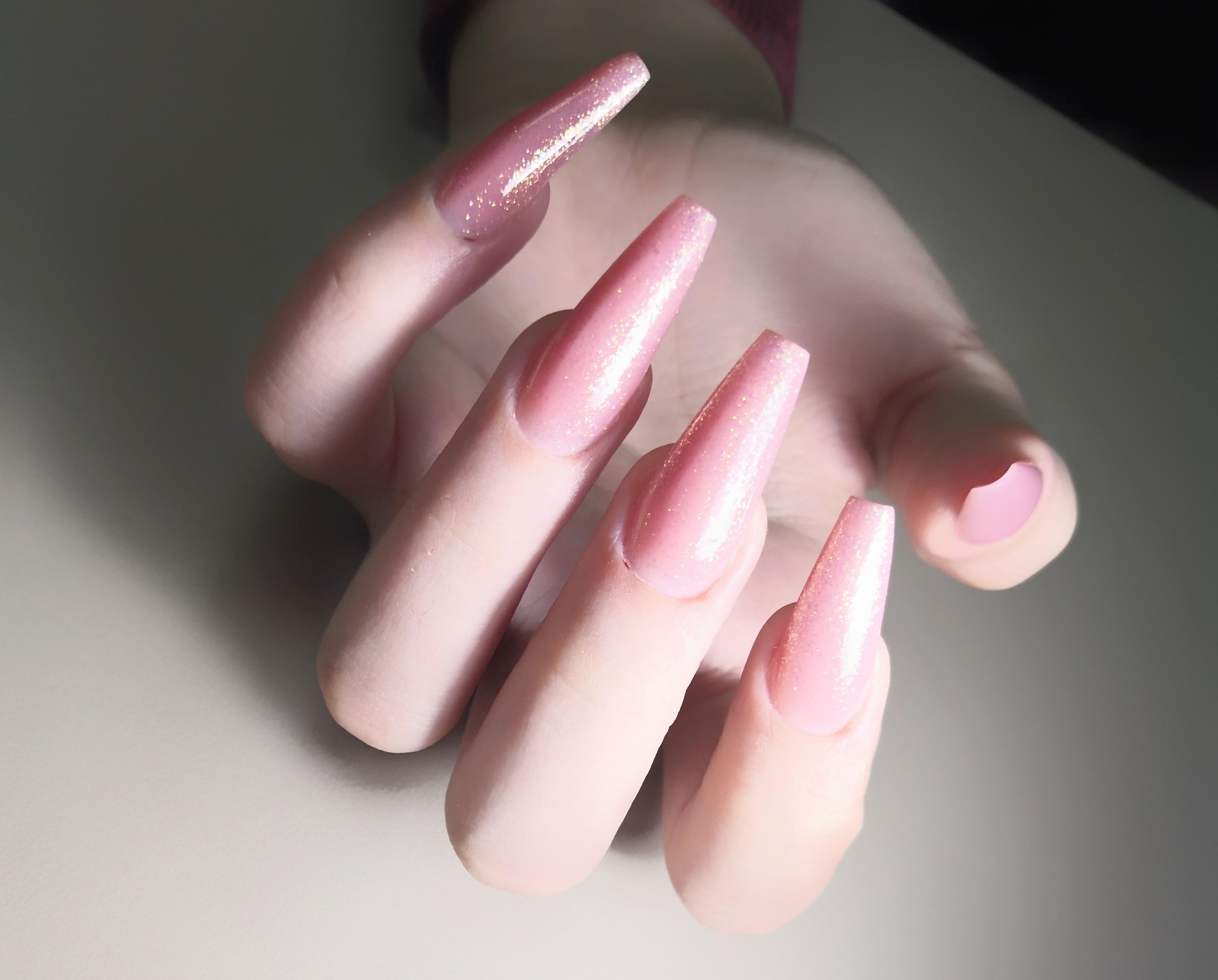 Маникюр на длинных ногтях в розовом цвете с золотыми блёстками.