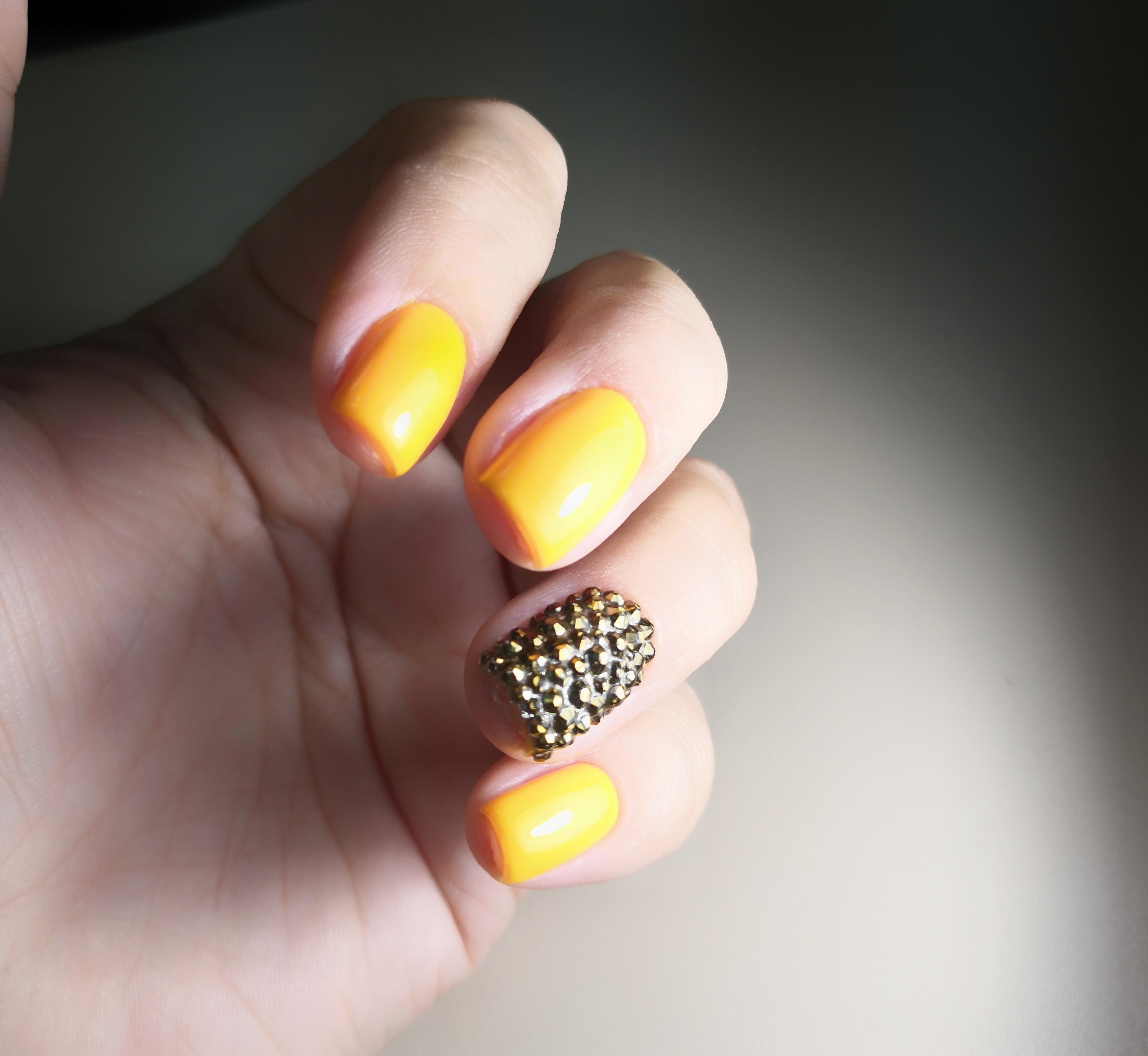 Маникюр в жёлтом цвете с объёмными стразами.