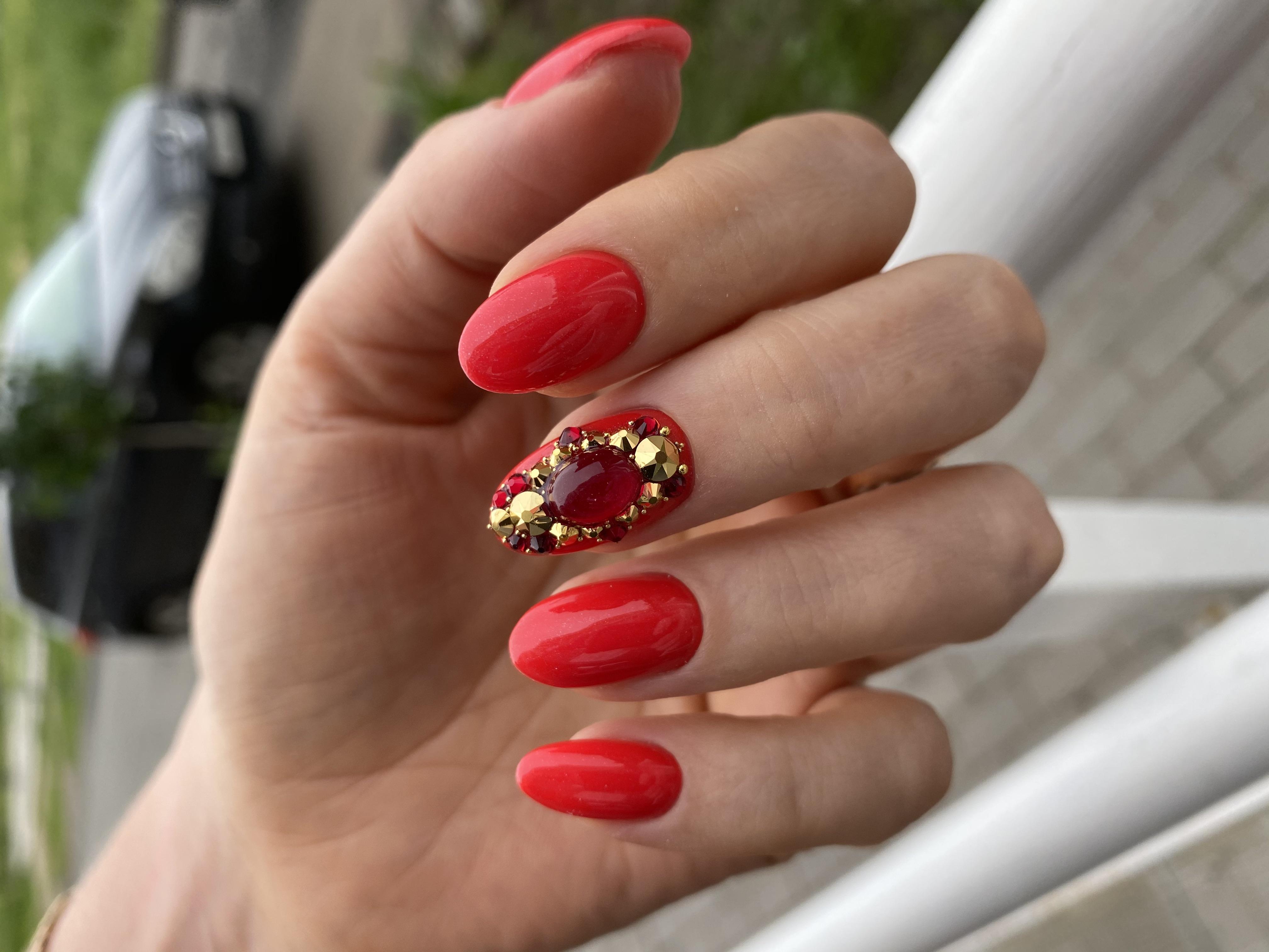 Маникюр со стразами в красном цвете на короткие ногти.
