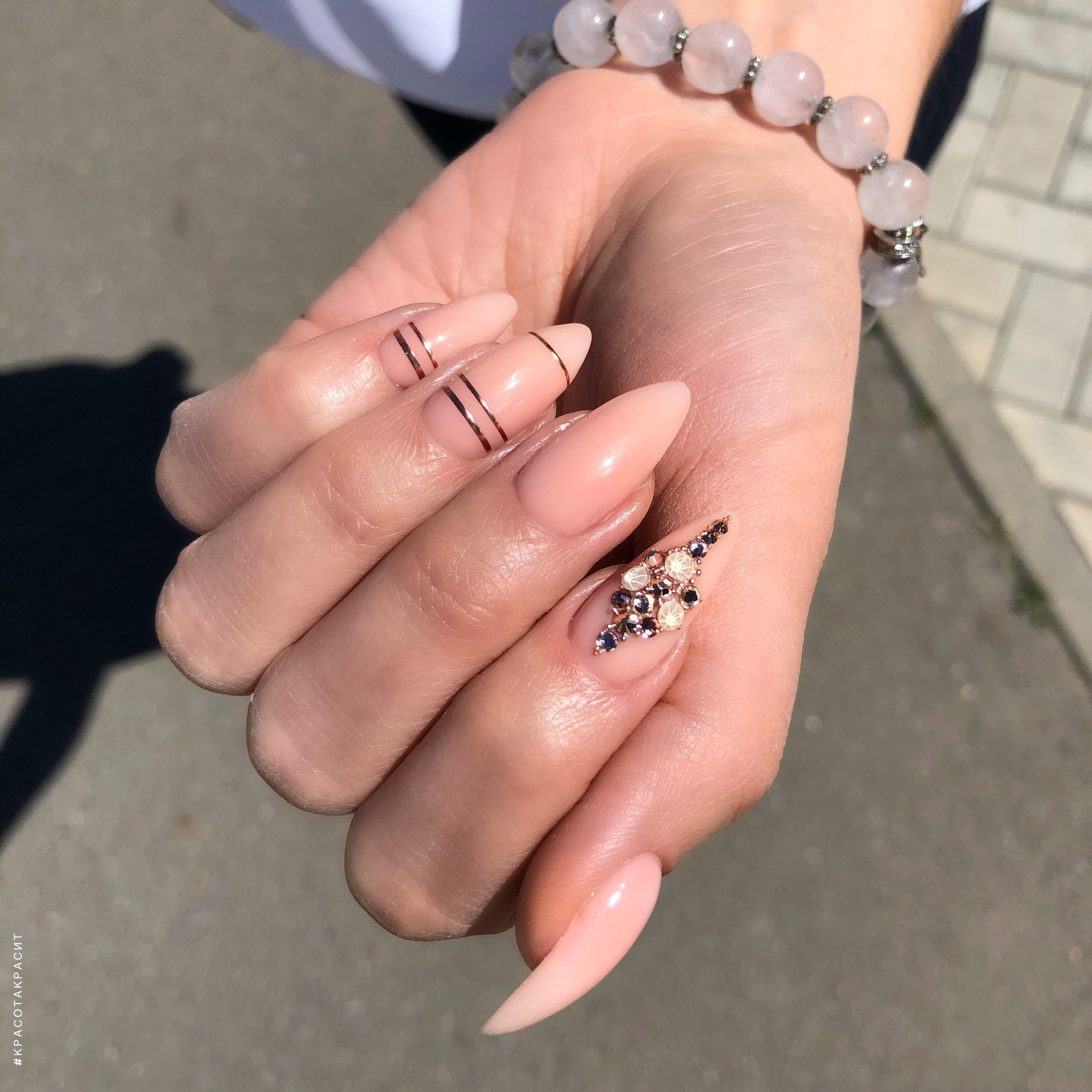 Нюдовый маникюр с золотыми полосками и стразами на длинные ногти.