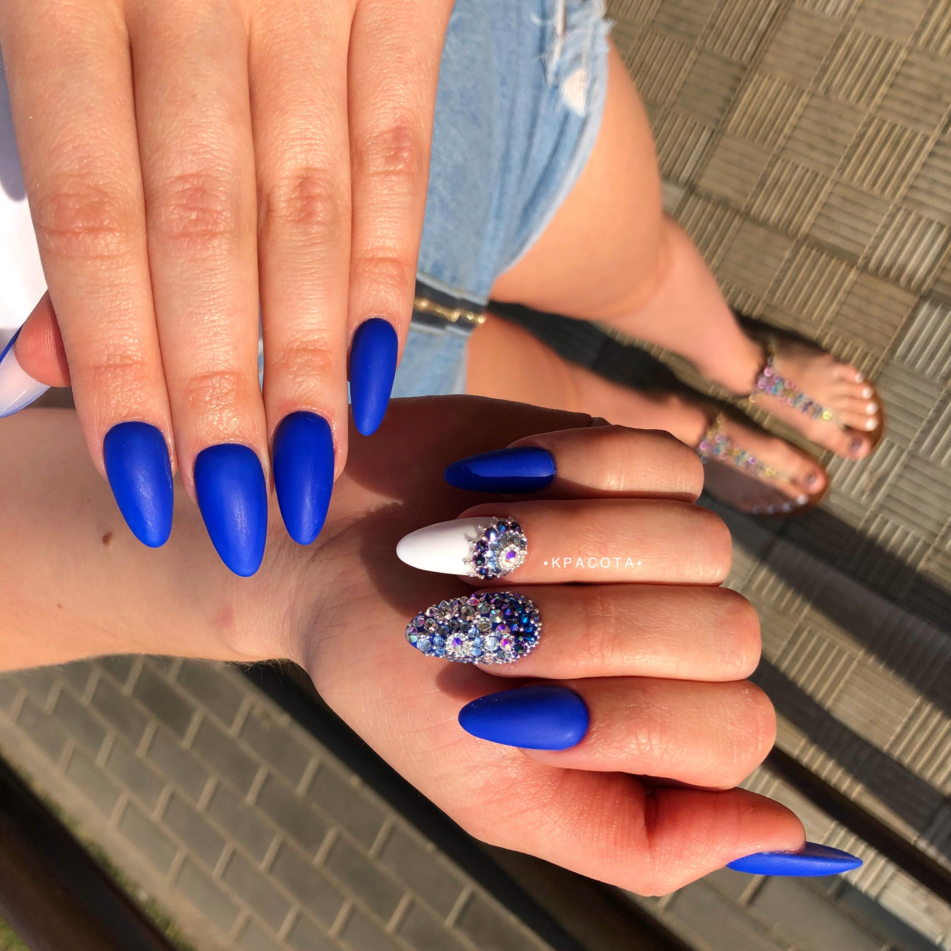 Матовый маникюр со стразами в синем цвете на длинные ногти.