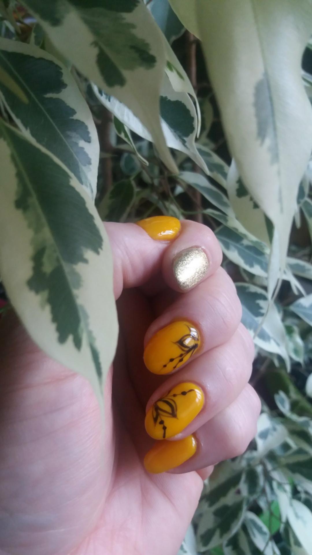 Маникюр с цветочным рисунком и золотыми блестками в оранжевом цвете.