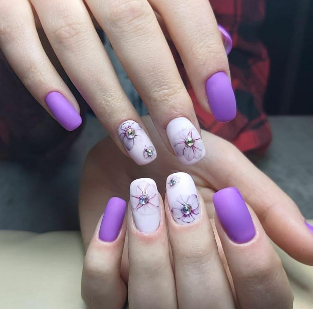 Матовый маникюр с цветочным рисунком и стразами в фиолетовом цвете.