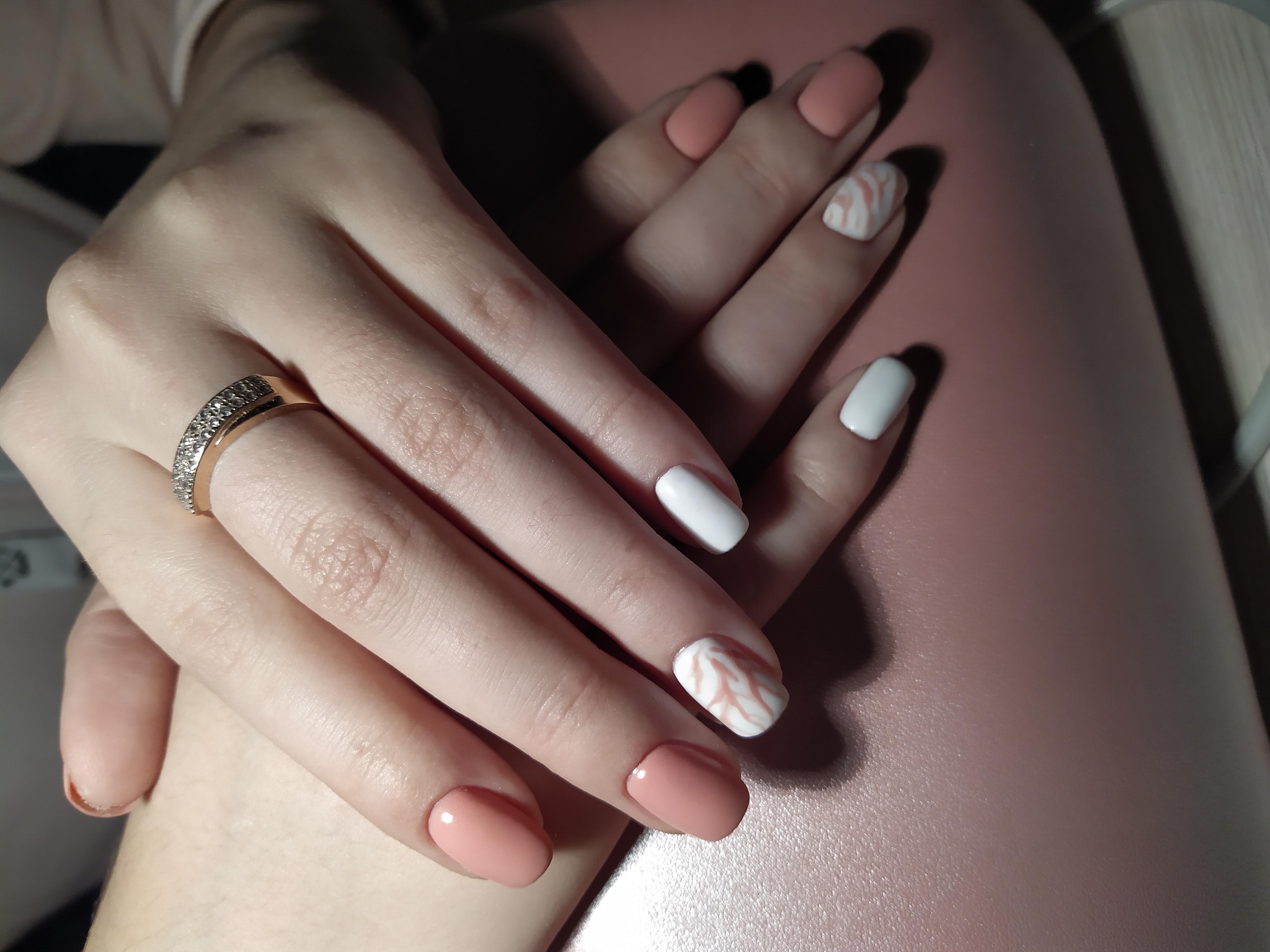 Маникюр в персиковом и белом цветах с абстрактным рисунком.