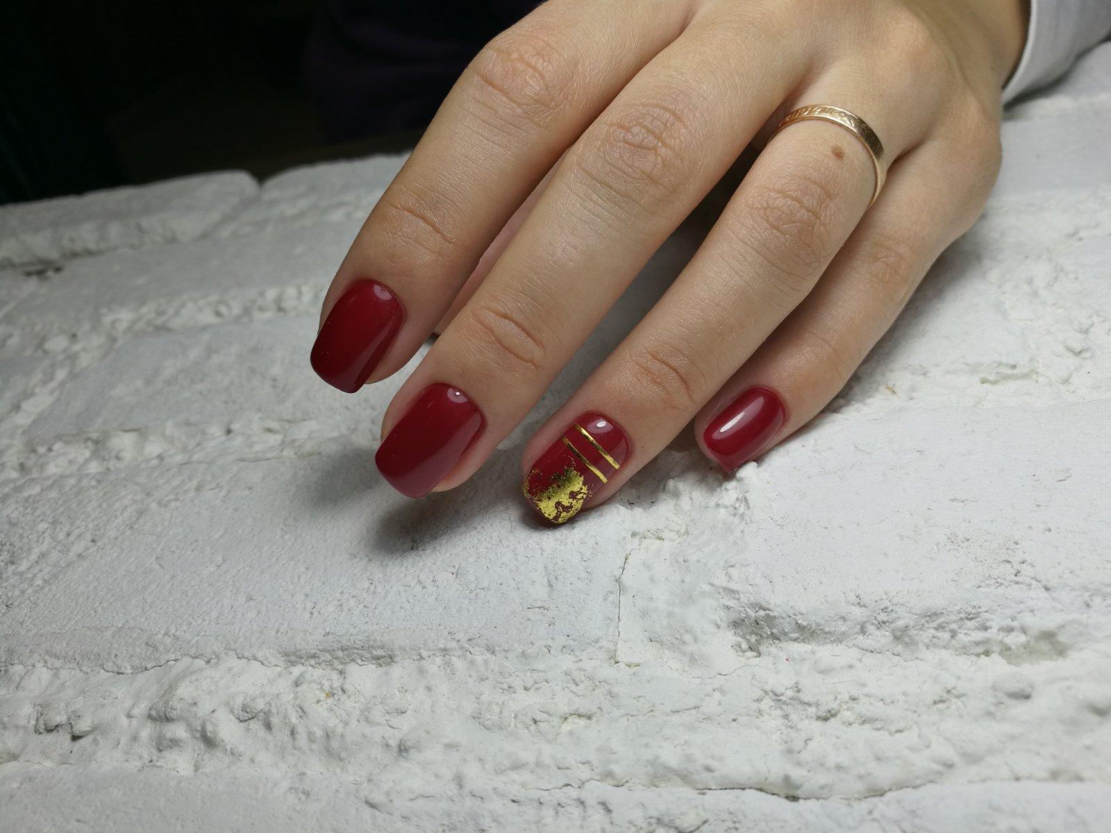 Маникюр в тёмно-красном цвете с золотой фольгой и полосками.