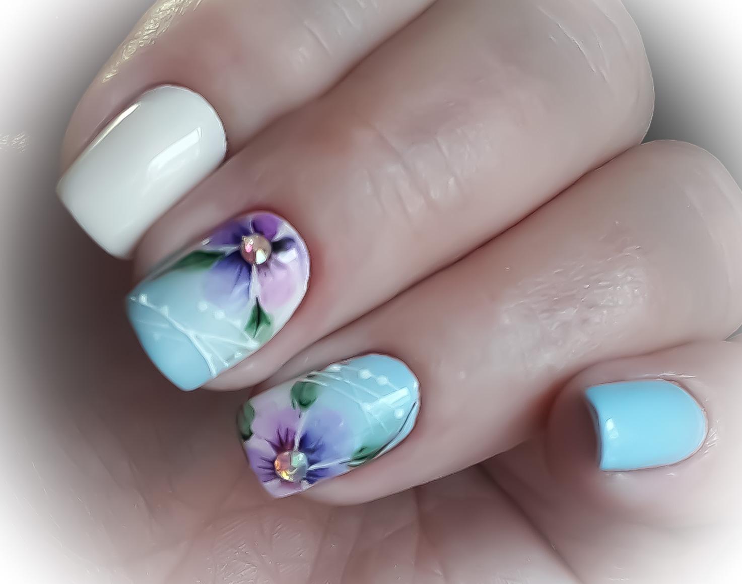 Маникюр с акварельным цветочным рисунком и стразами в голубом цвете.