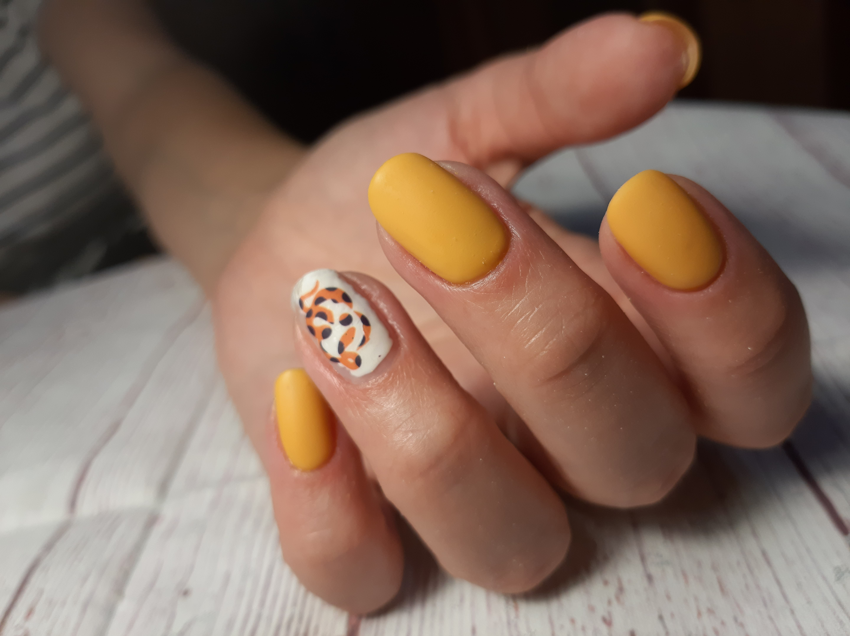 Матовый маникюр с анималистичным принтом в желтом цвете на короткие ногти.
