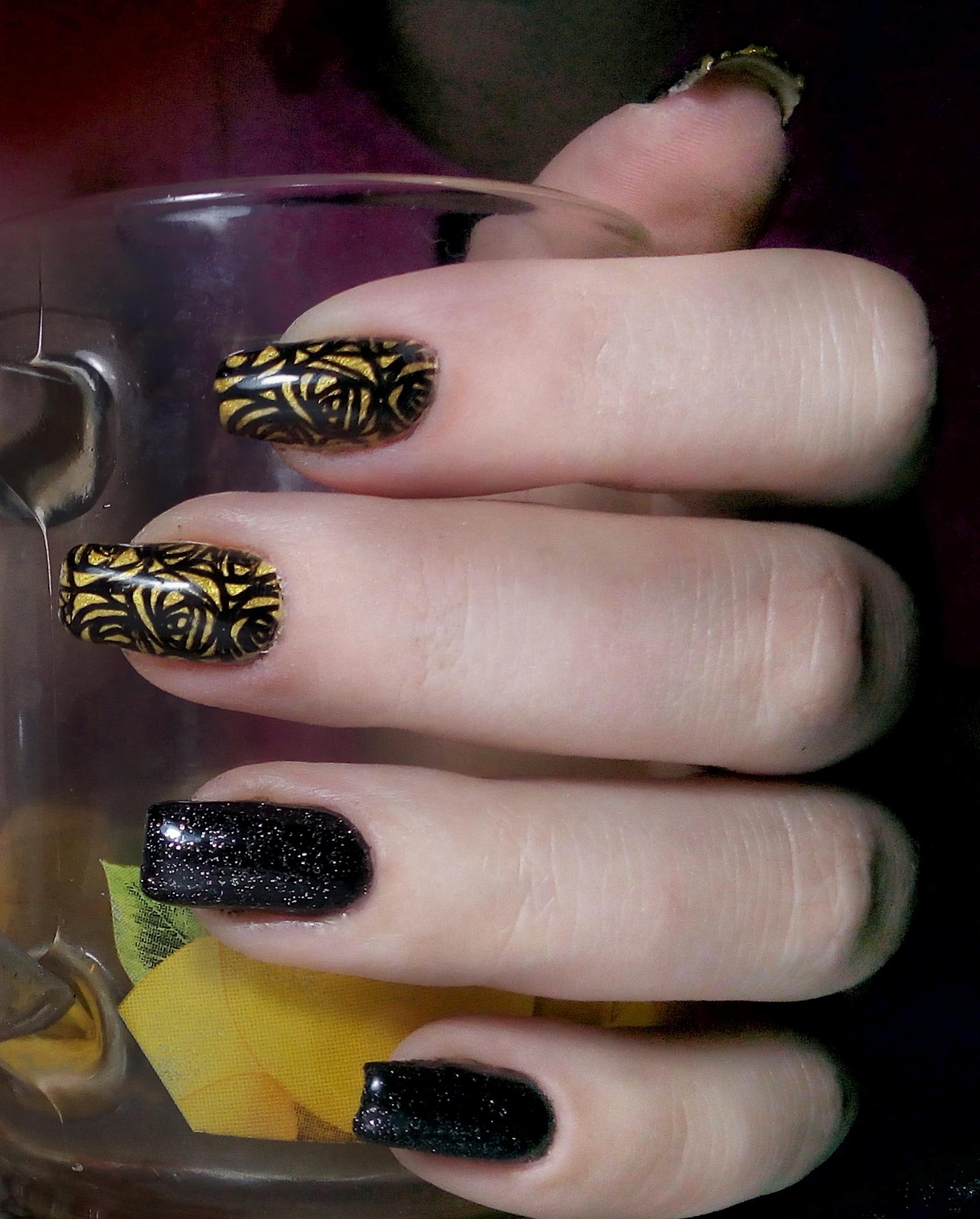 Маникюр в чёрно-золотых тонах с абстрактным рисунком и блёстками.