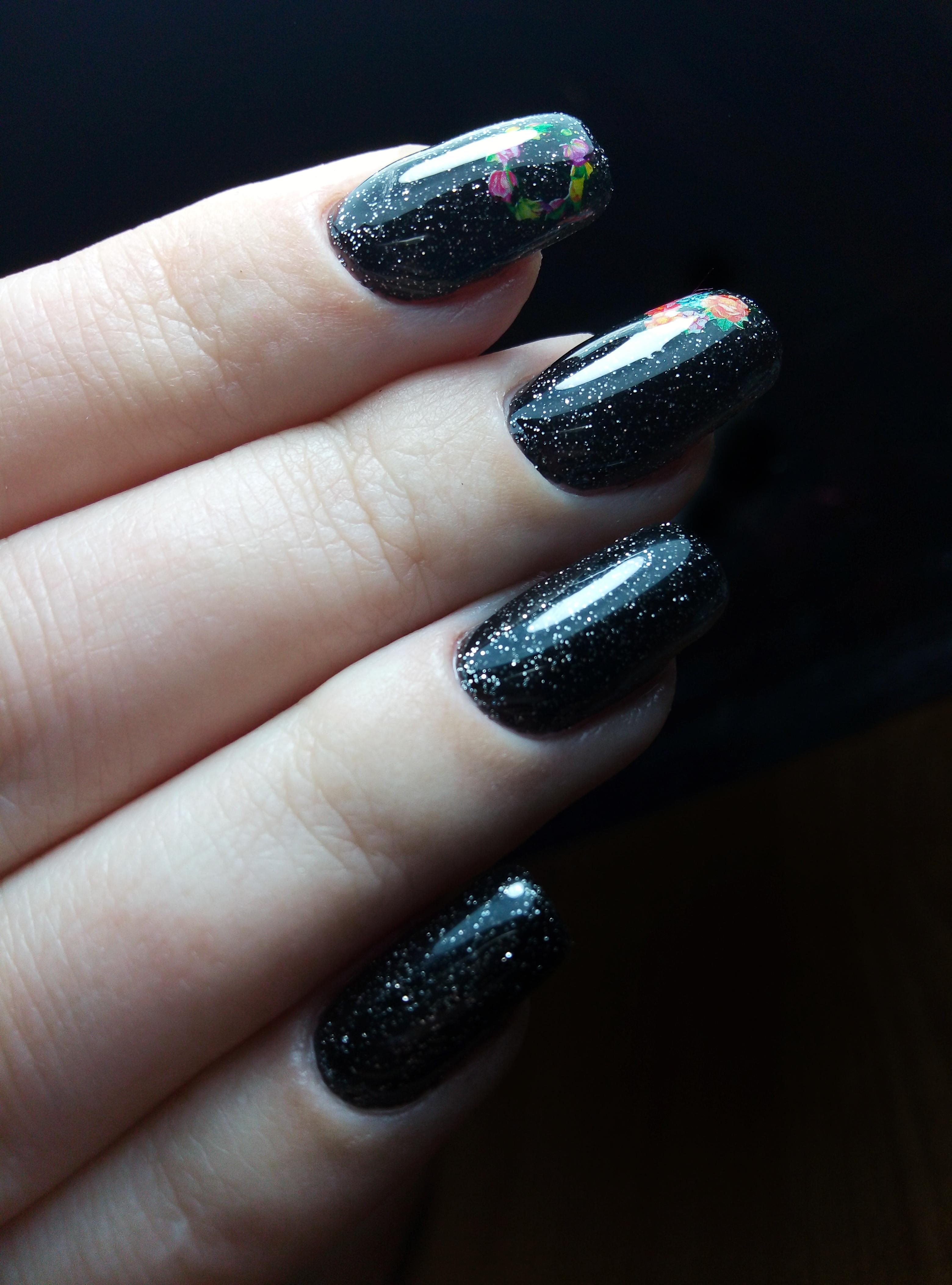 Маникюр в чёрном цвете с цветочными слайдерами и блёстками.