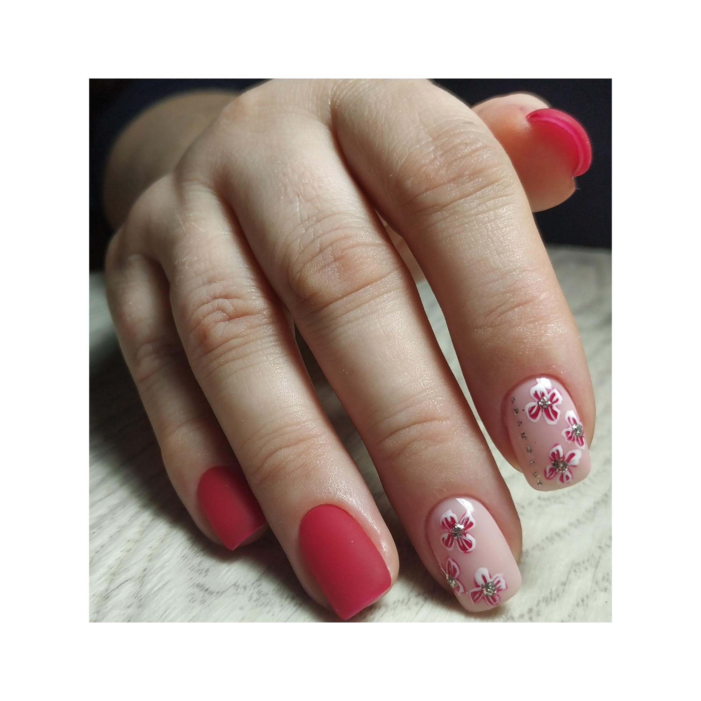 Матовый маникюр с цветочным рисунком в красном цвете.