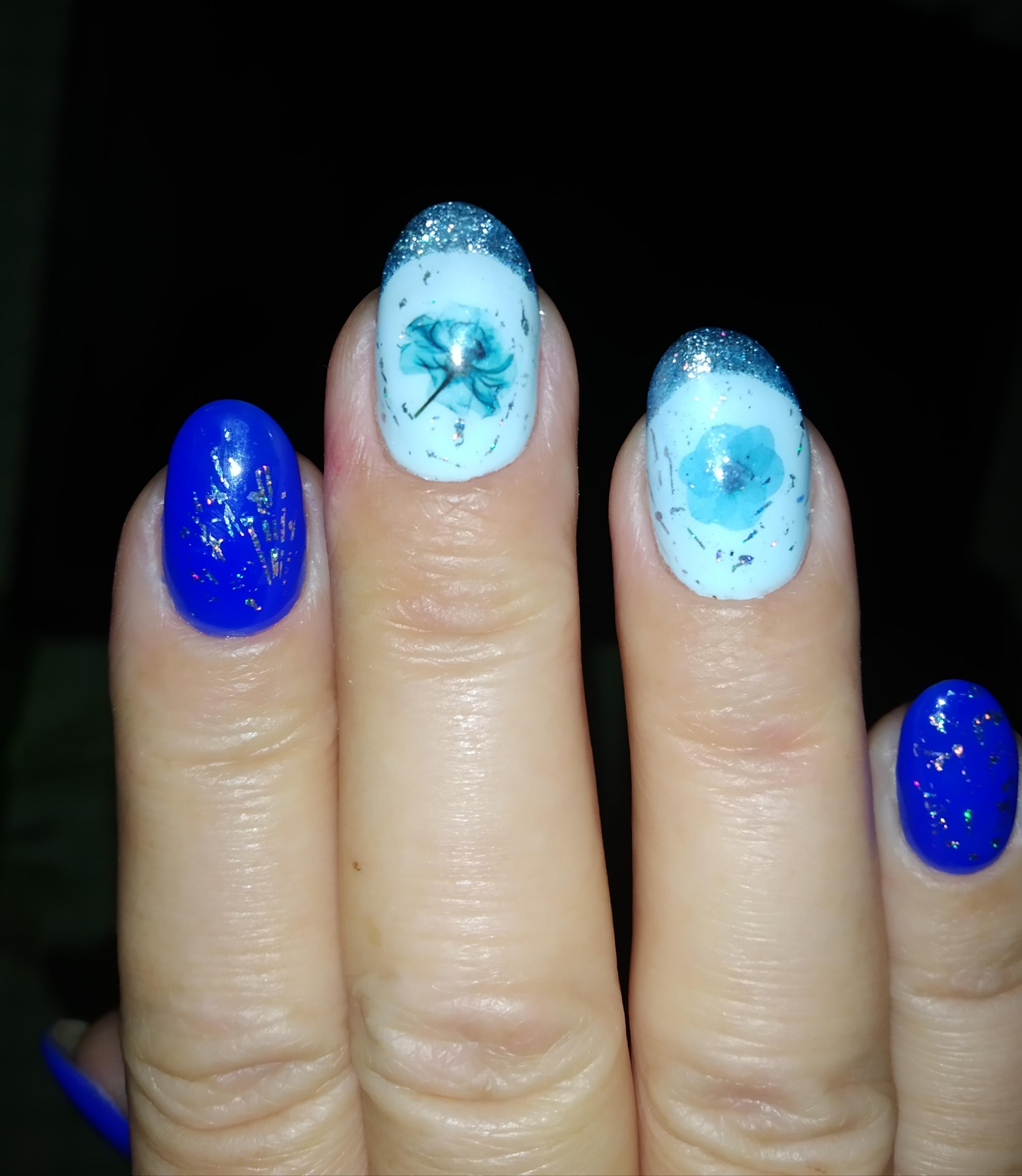 Маникюр с цветочными слайдерами, френч-дизайном и блёстками в синем цвете на короткие ногти.