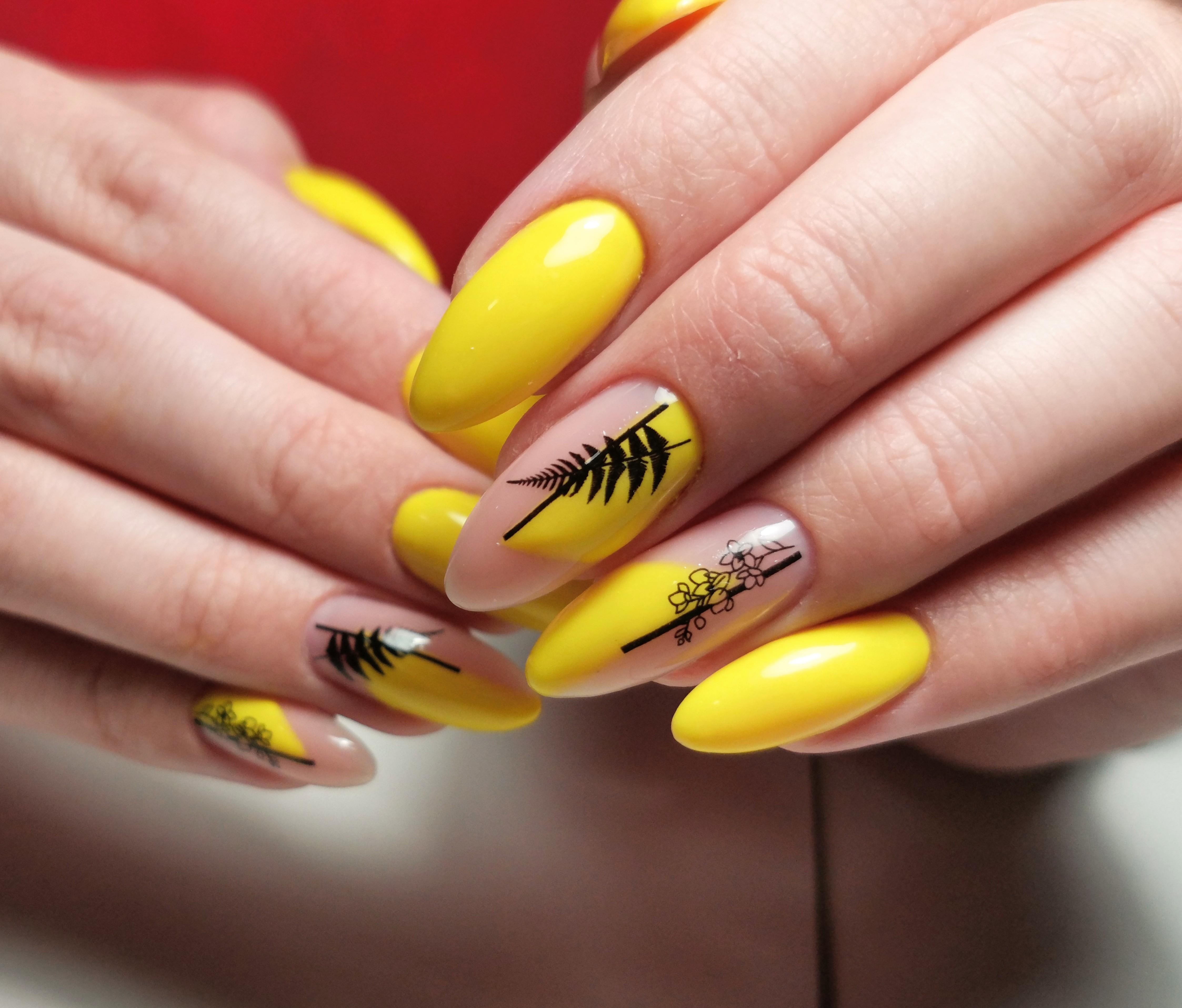 Маникюр с растительными слайдерами в желтом цвете.