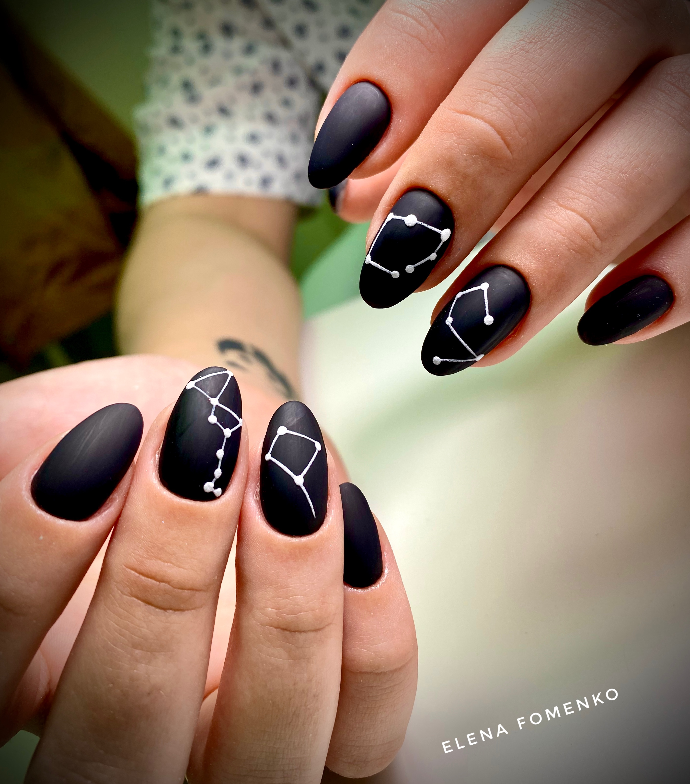 Матовый маникюр с созвездиями в черном цвете.