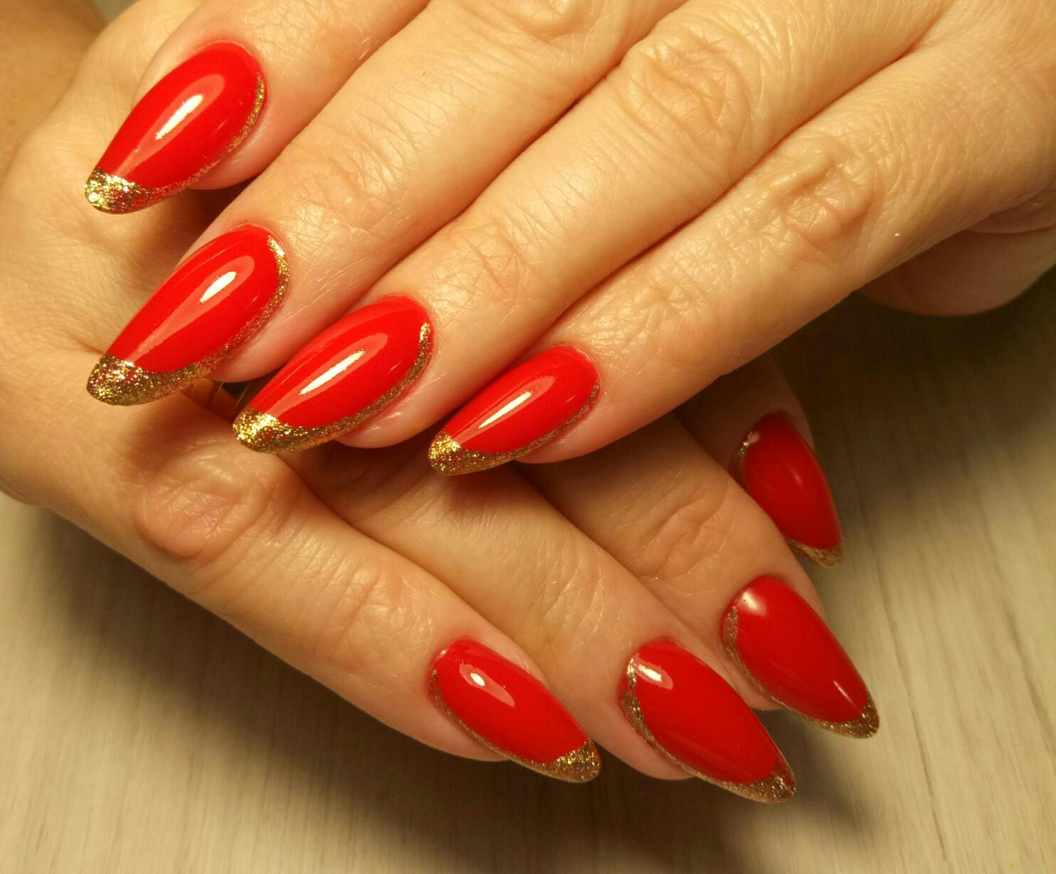 Маникюр с золотыми блестками в красном цвете.