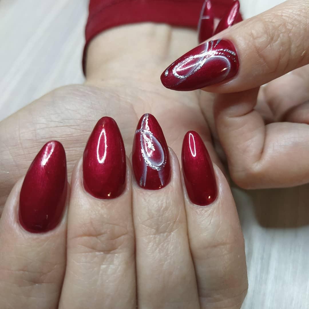 Маникюр с рисунком и блестками в темно-красном цвете на длинные ногти.