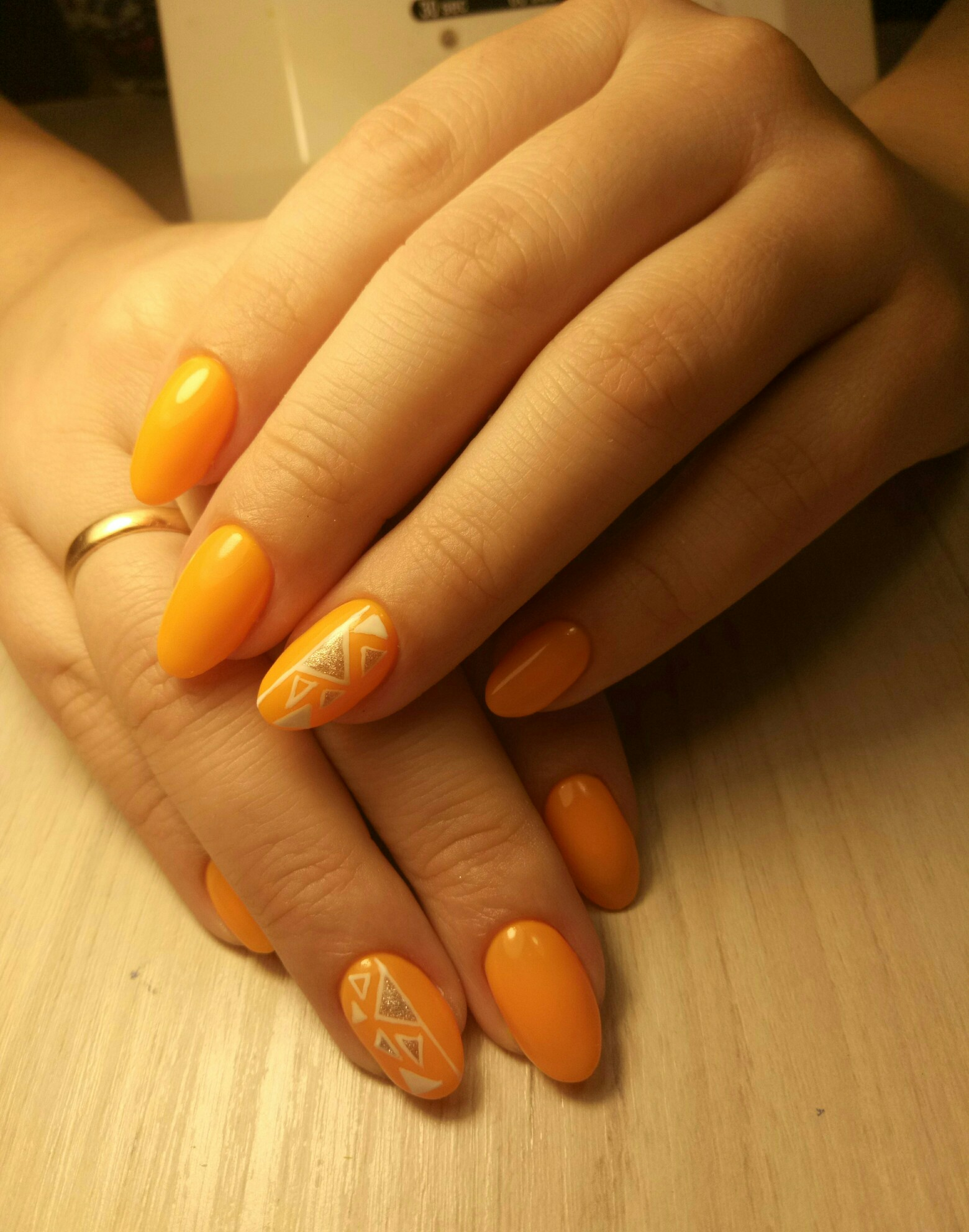 Геометрический маникюр с серебряными блестками в оранжевом цвете.