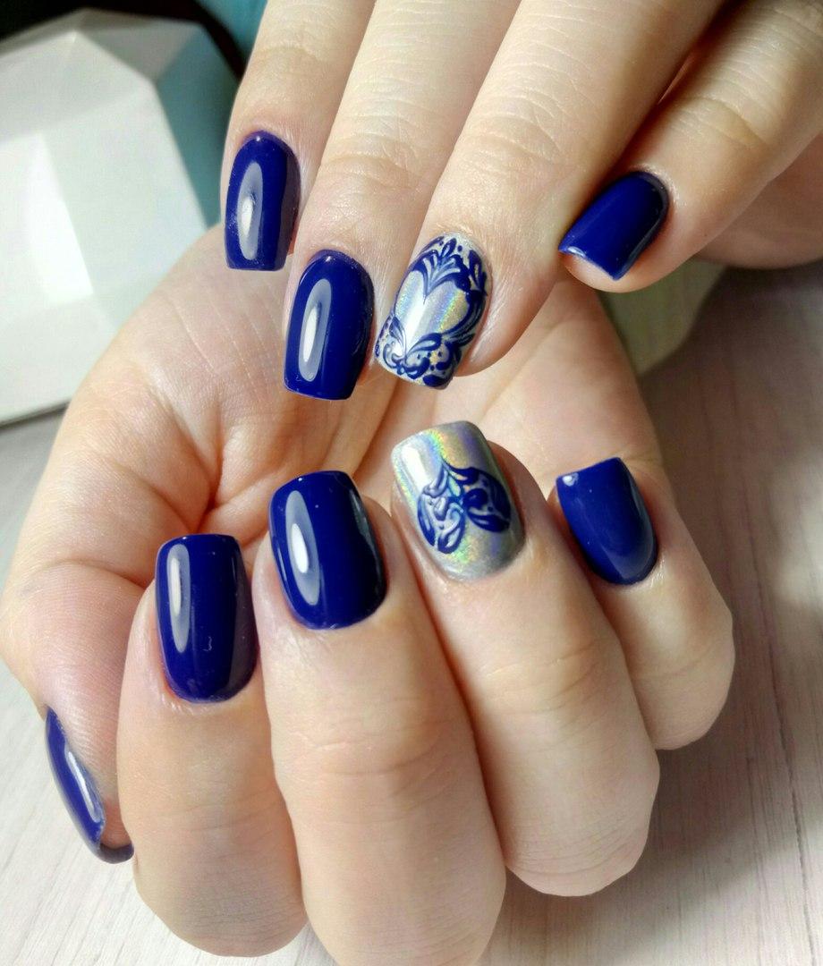 Маникюр с серебряной втиркой и сердечками в синем цвете.
