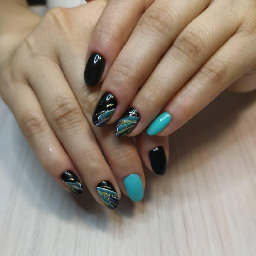 Маникюр с геометрическим рисунком и золотыми блестками в черном цвете на короткие ногти.