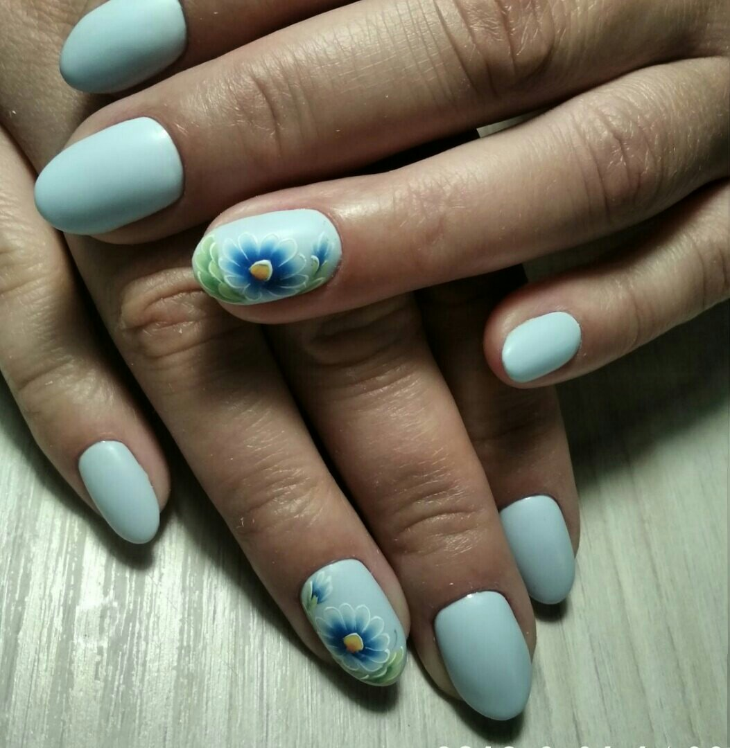 Маникюр с цветочным рисунком в голубом цвете.