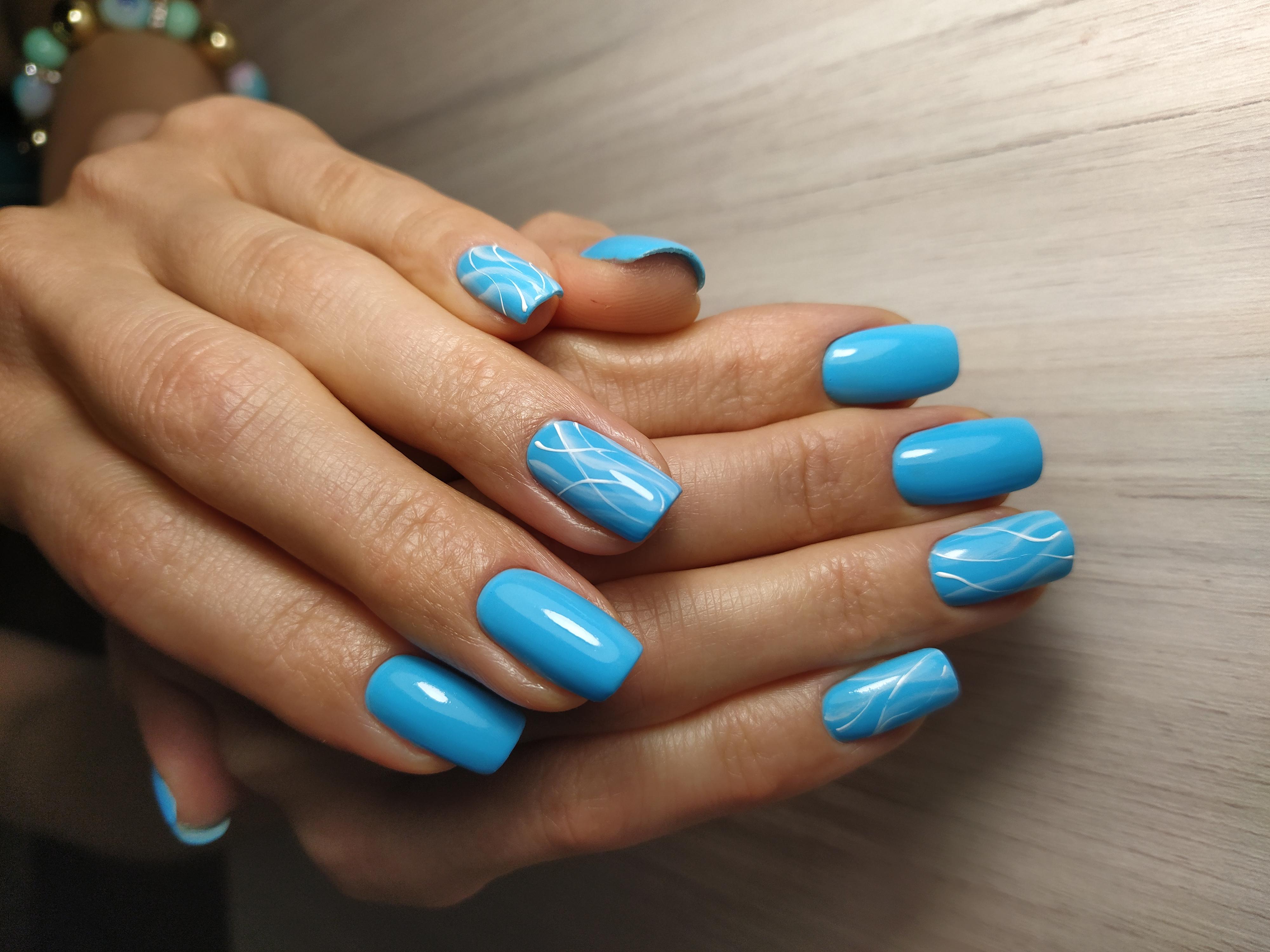Маникюр рисунком в голубом цвете на длинные ногти.