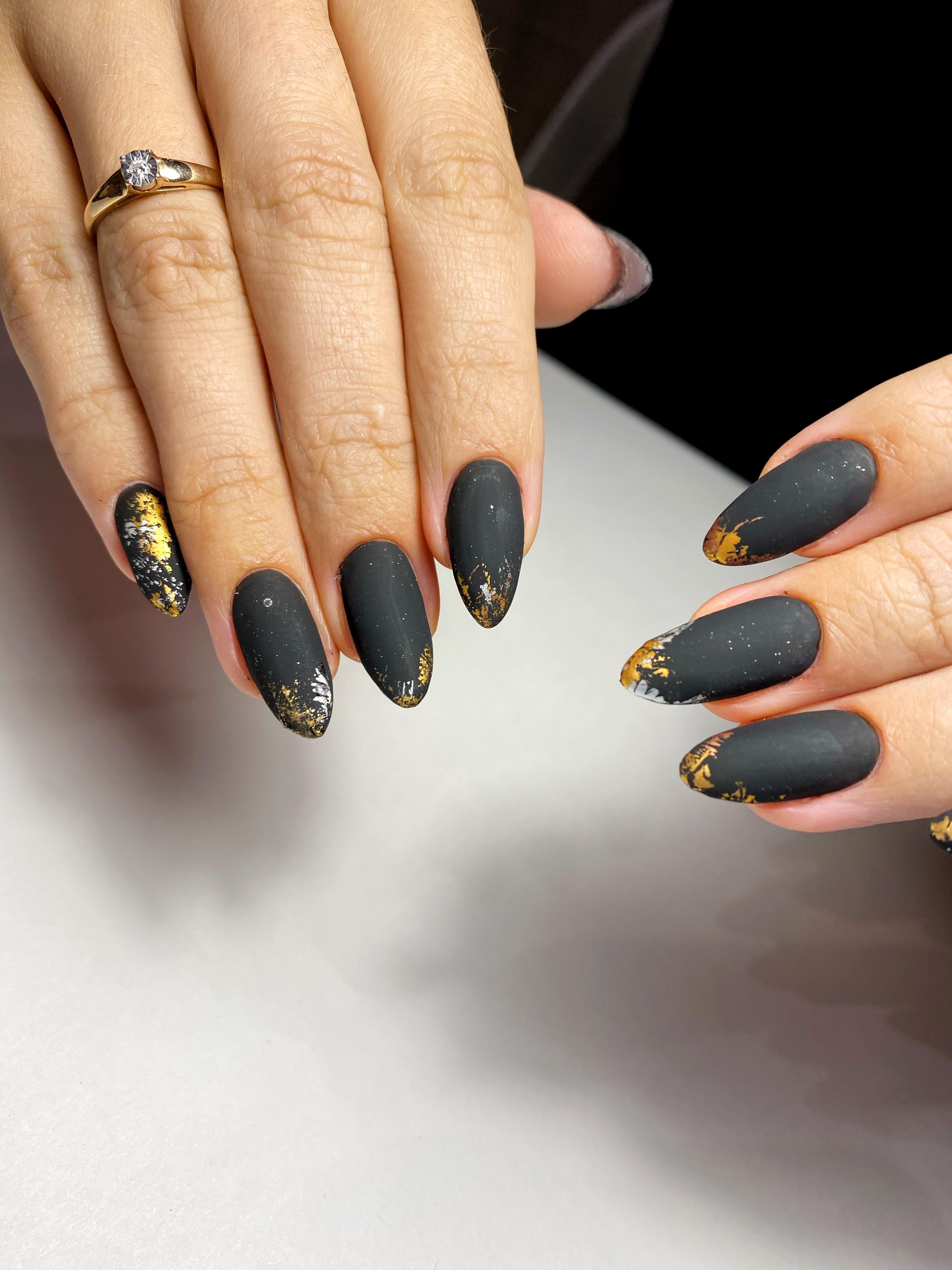 Матовый маникюр с золотой фольгой в черном цвете на длинные ногти.