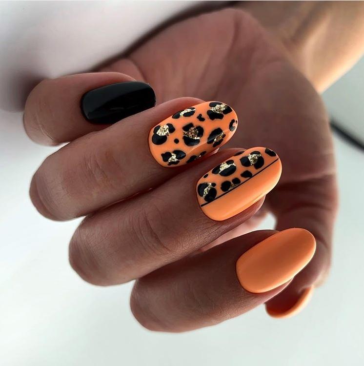 Маникюр с леопардовым принтом и блестками в оранжевом цвете на короткие ногти.