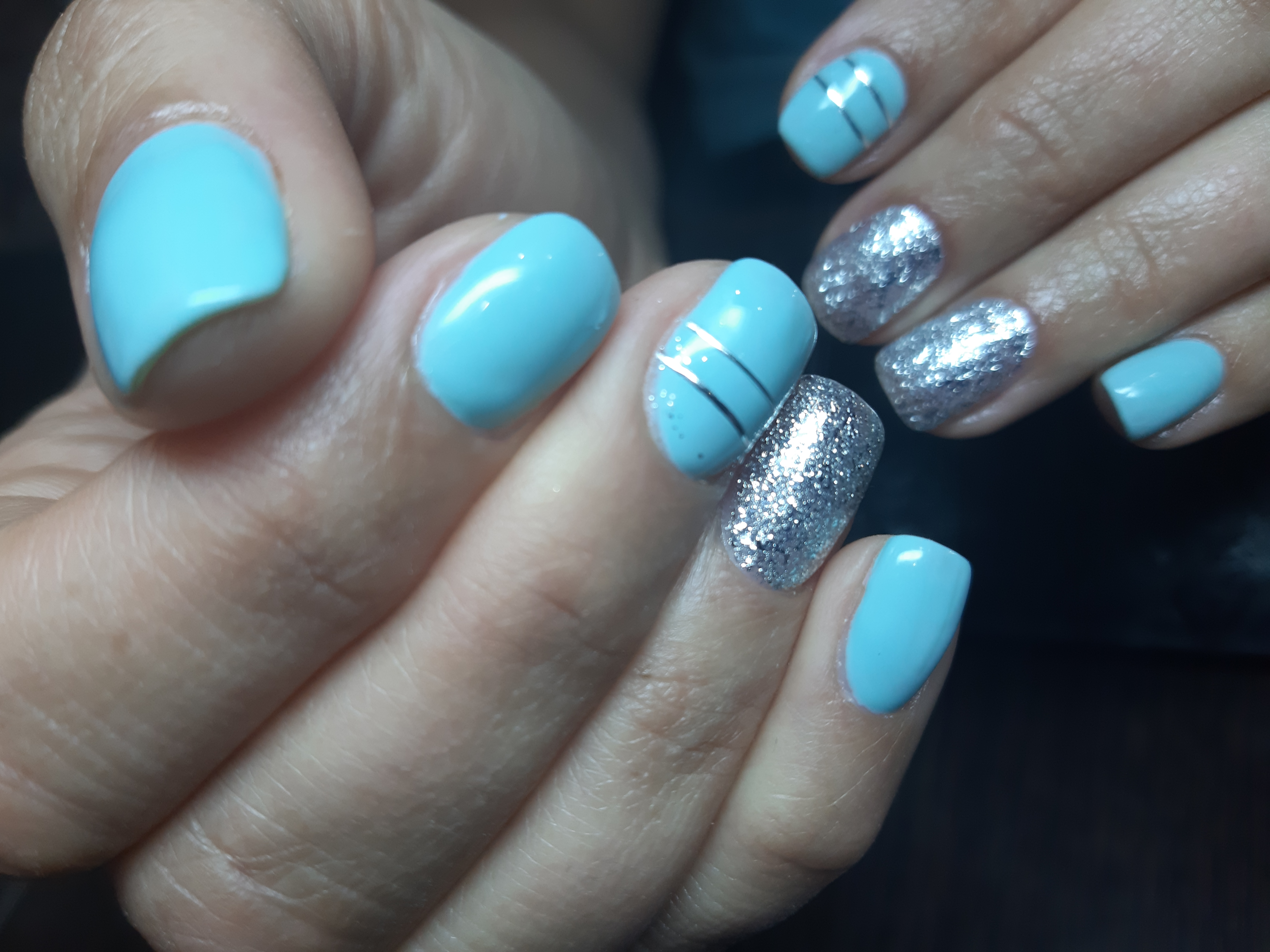 Маникюр с серебряными полосками и блестками в голубом цвете на короткие ногти.