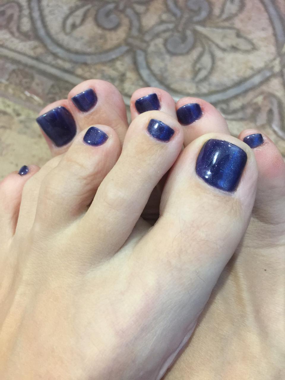 Педикюр с блестками в темно-синем цвете.
