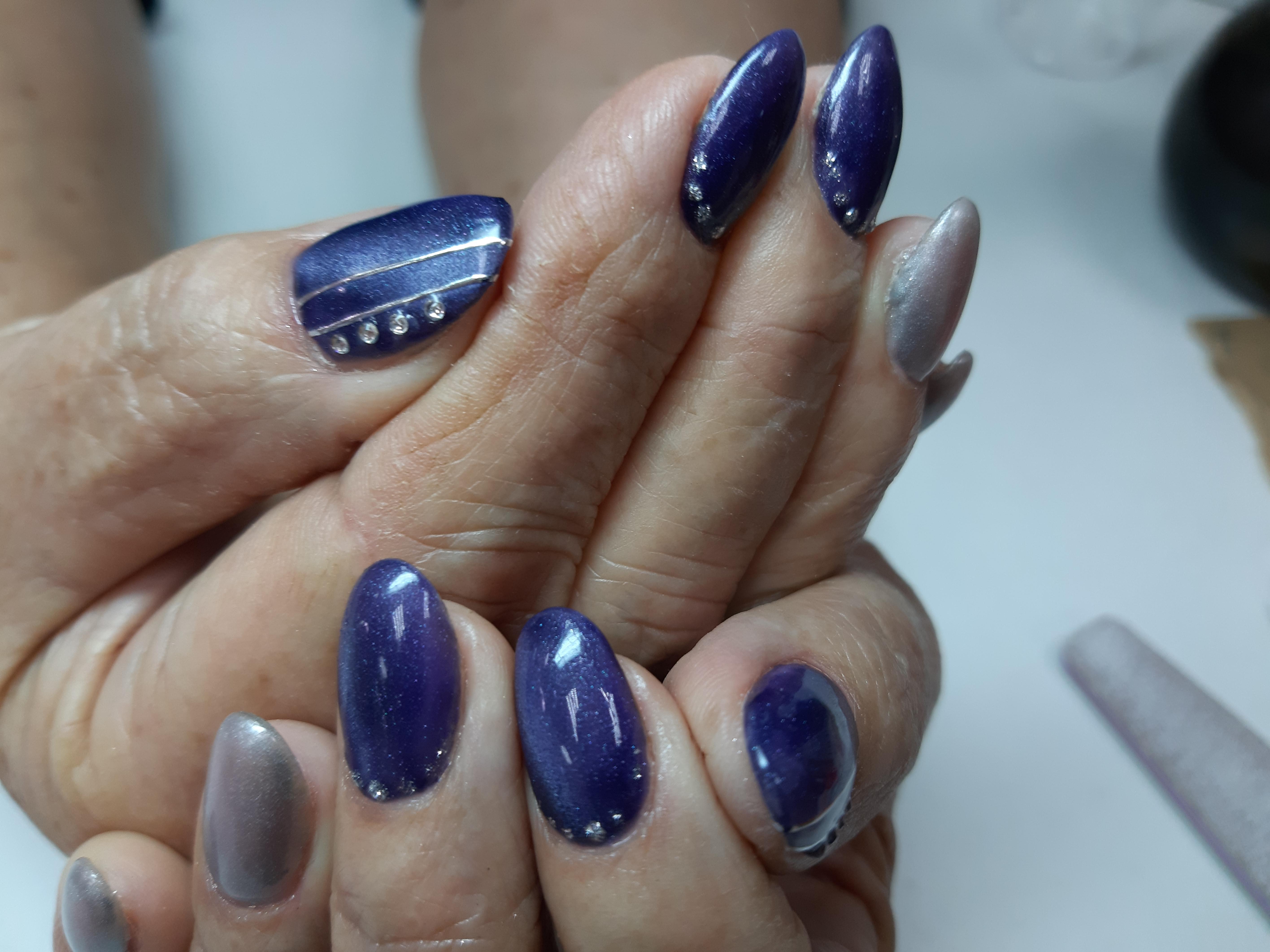 Маникюр с серебряными блестками и стразами в фиолетовом цвете.