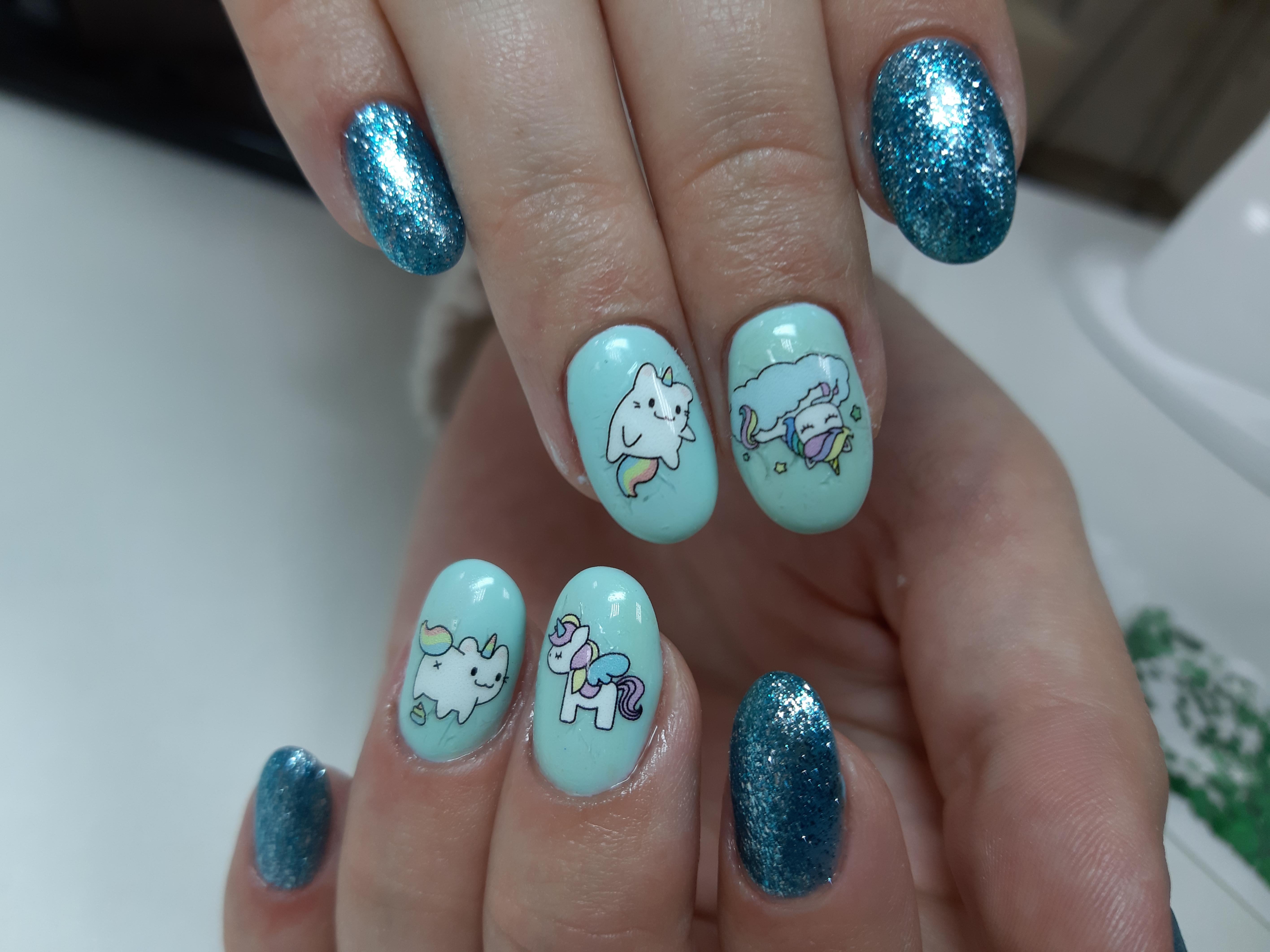 Маникюр с мультяшными слайдерами и блестками в голубом цвете.