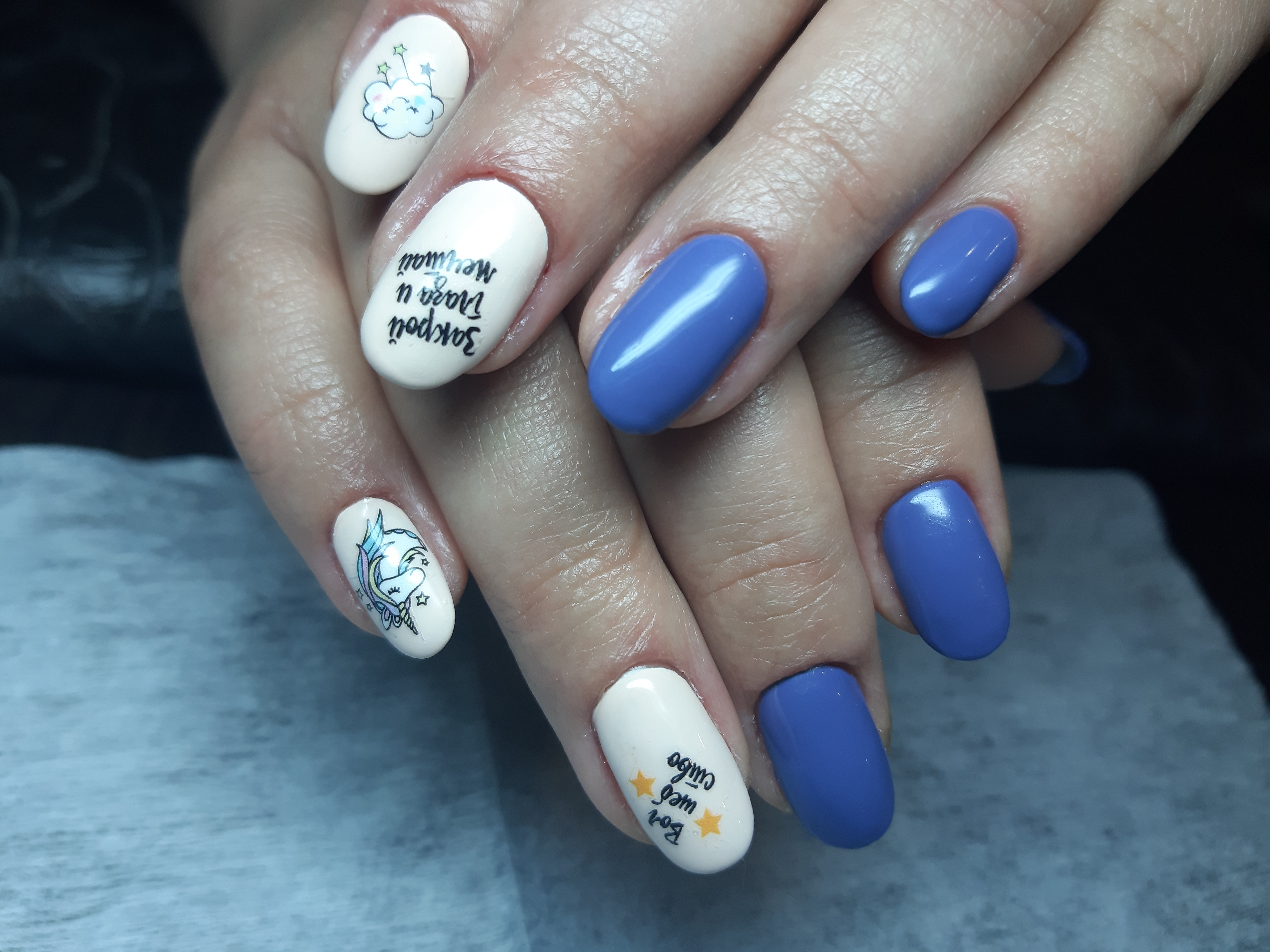 Маникюр со слайдерами и надписями в синем цвете на короткие ногти.