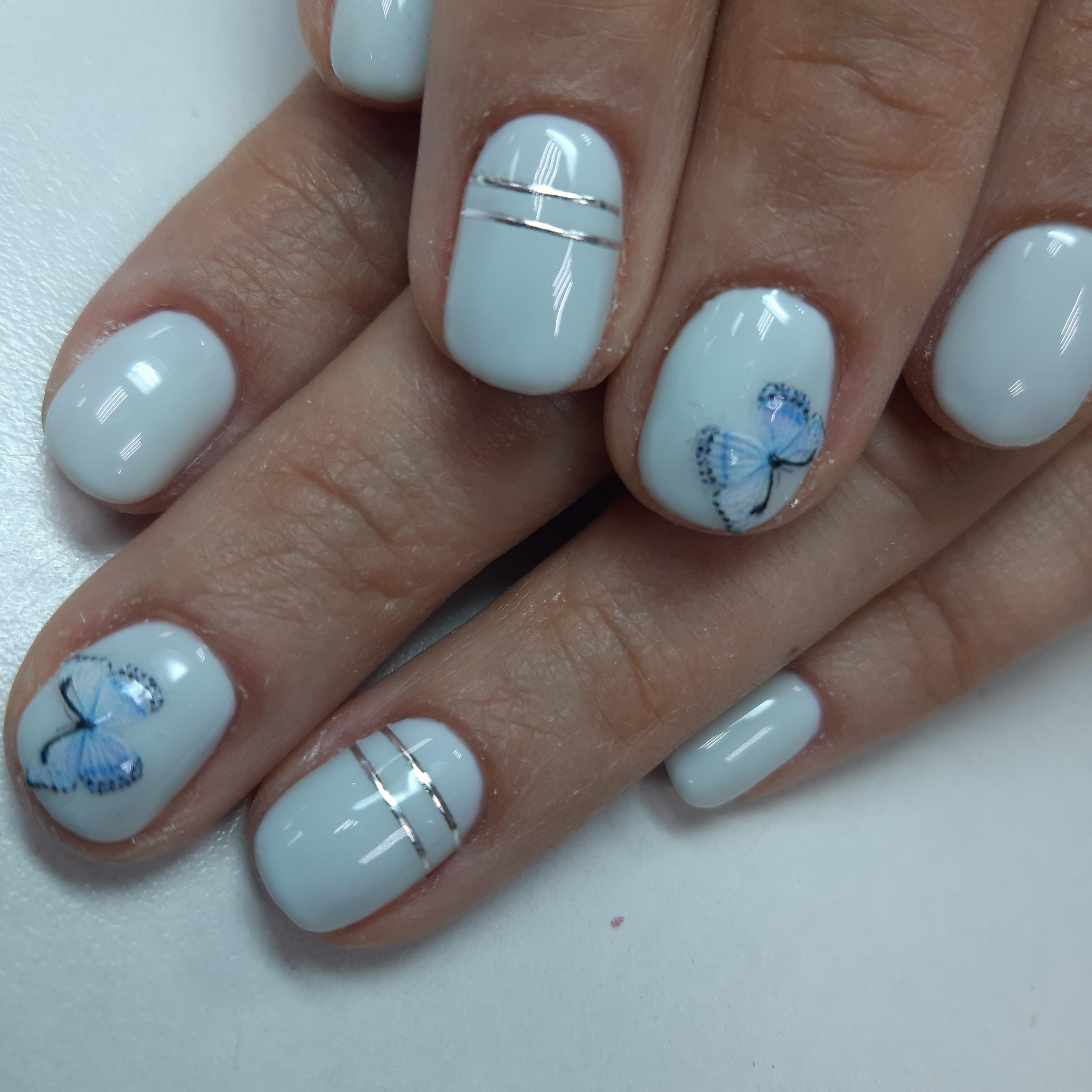 Маникюр с бабочками и серебряными полосками в белом цвете.