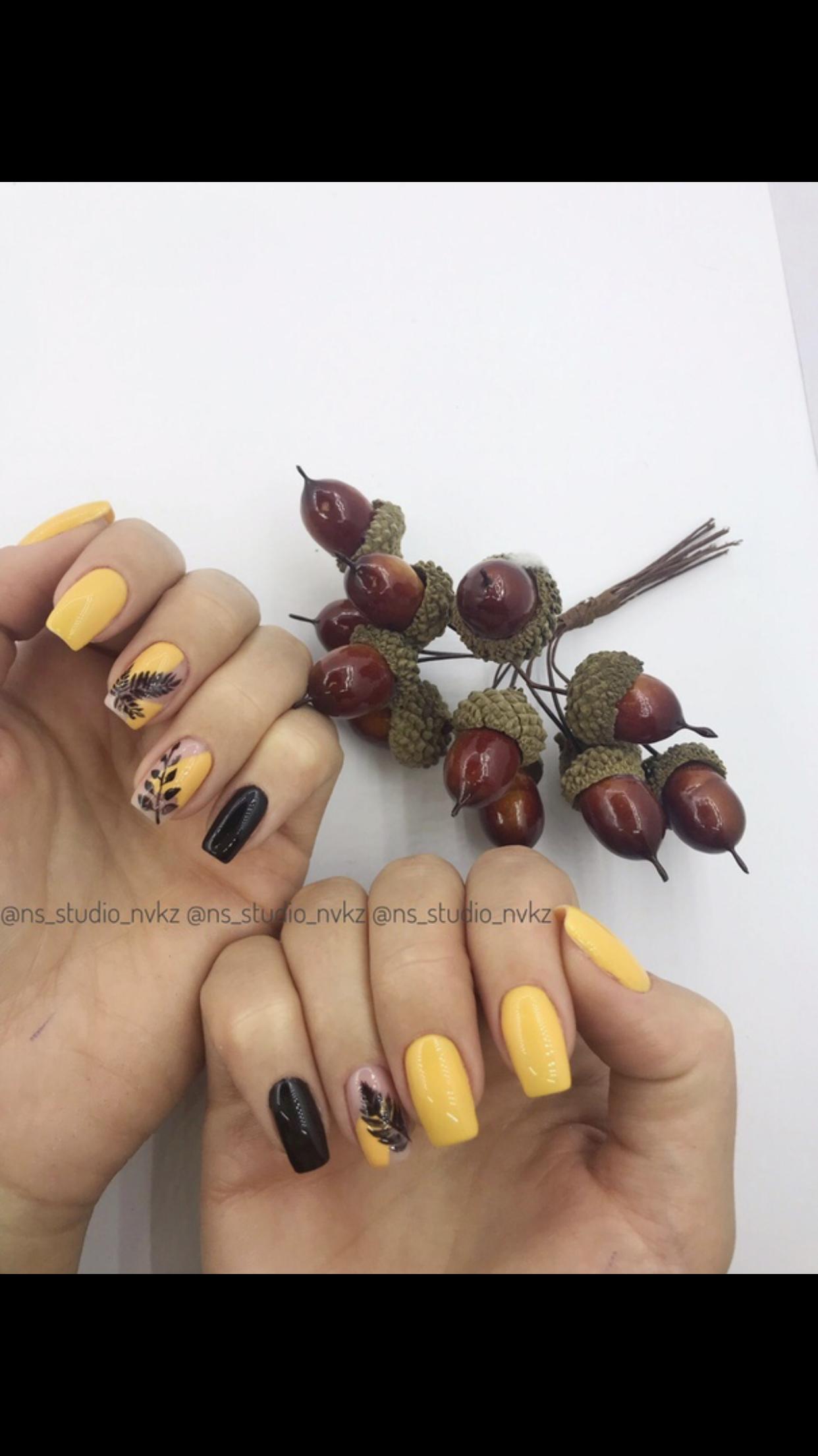 Маникюр с контрастным сочетанием чёрного и жёлтого цветов и растительными слайдерами.